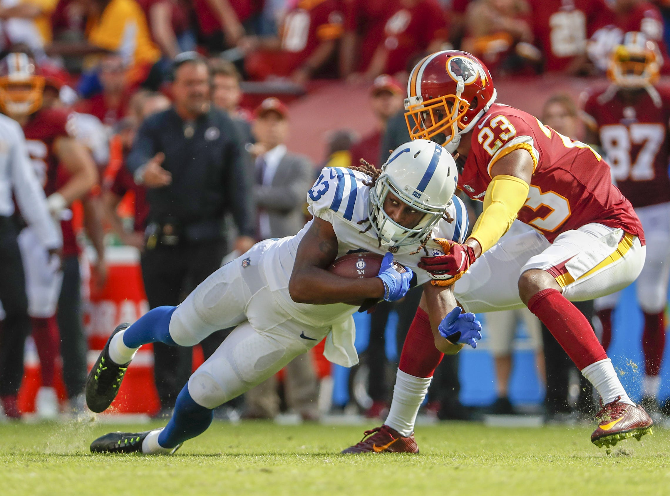 Indianapolis Colts wide receiver T.Y. Hilton (13) makes an effort for more yardage as he's contacted by Washington Redskins cornerback Quinton Dunbar (23) during second half action. The Indianapolis Colts play the Washington Redskins at FedEx Field in Landover, MD., Sunday, Sept. 16, 2018. Colts won the game 21-9.