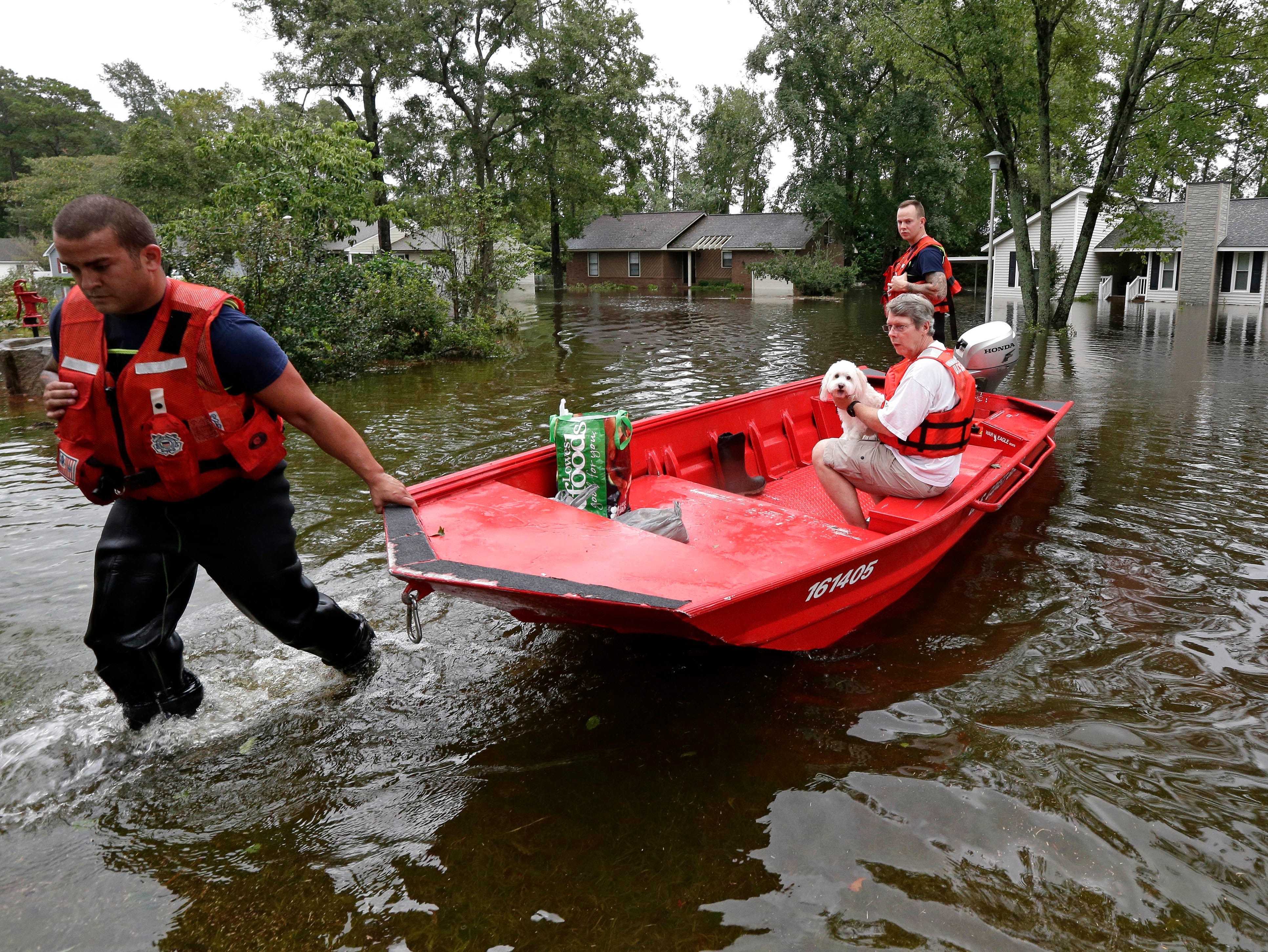 Roger Hedgepeth and his dog Bodie are assisted by members of the U.S. Coast Guard in Lumberton, N.C., Sunday, Sept. 16, 2018, following flooding from Hurricane Florence. Hedgepeth was moved to higher ground.
