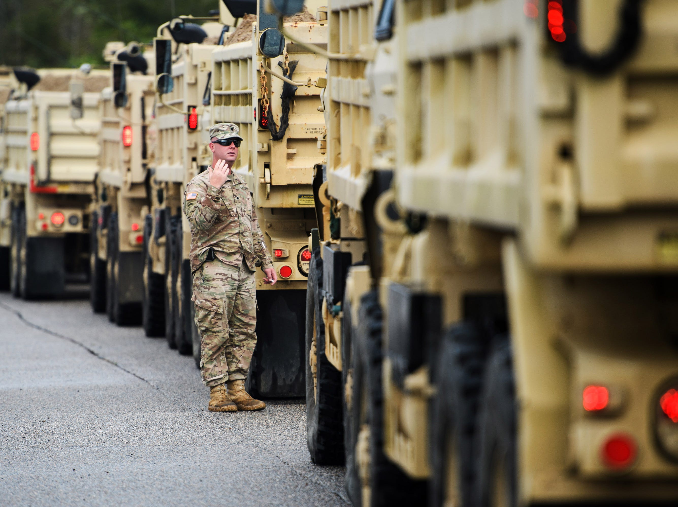 Sept 16, 2018, North Myrtle Beach, SC, A South Carolina Army National Guard directs trucks full of sand along U.S. 501 South outside of Conway in preparation of rising water levels on the Waccamaw River due to Tropical Depression Florence.