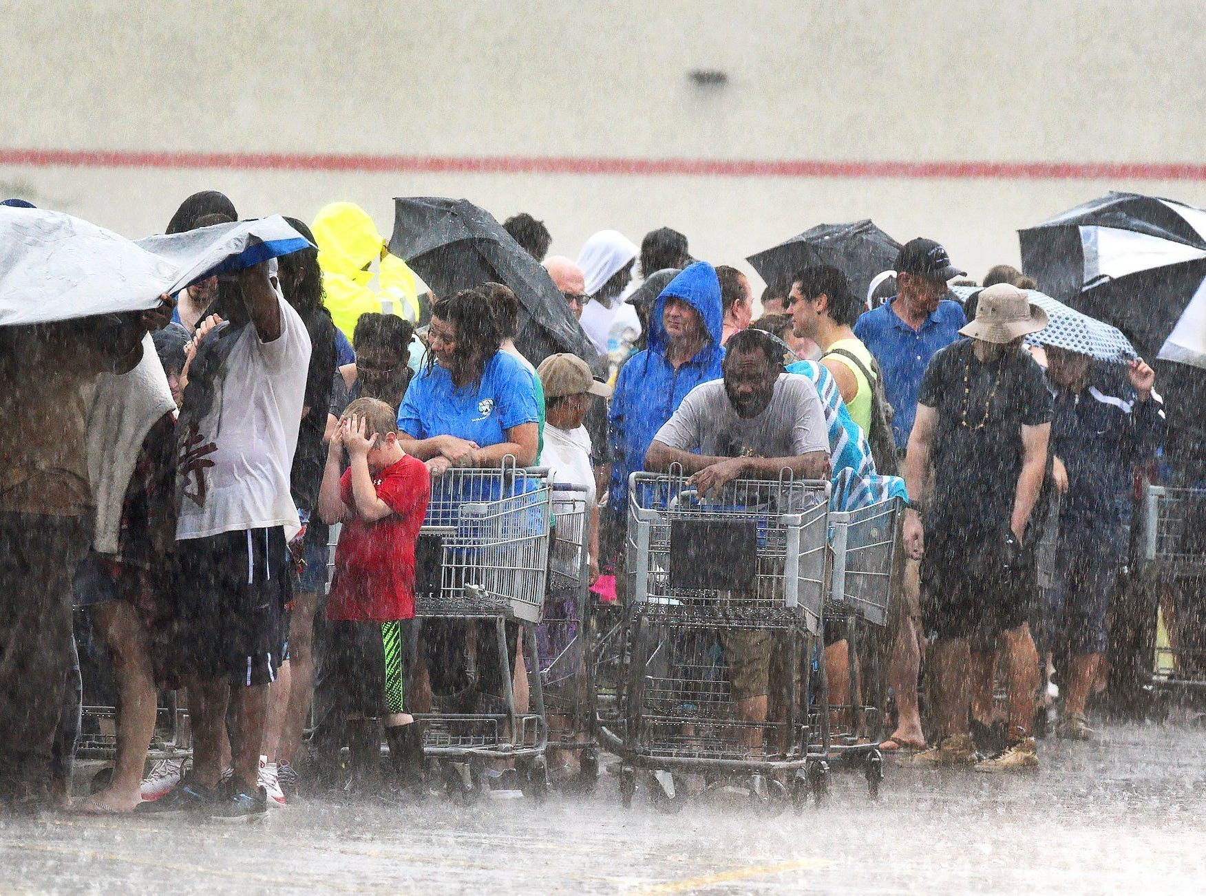 The rain continued in southeastern North Carolina Sunday, Sept. 16, 2018, in Rocky Point, N.C. as customers waiting in line at the local grocery store get pelted during a deluge from Tropical Storm Florence.