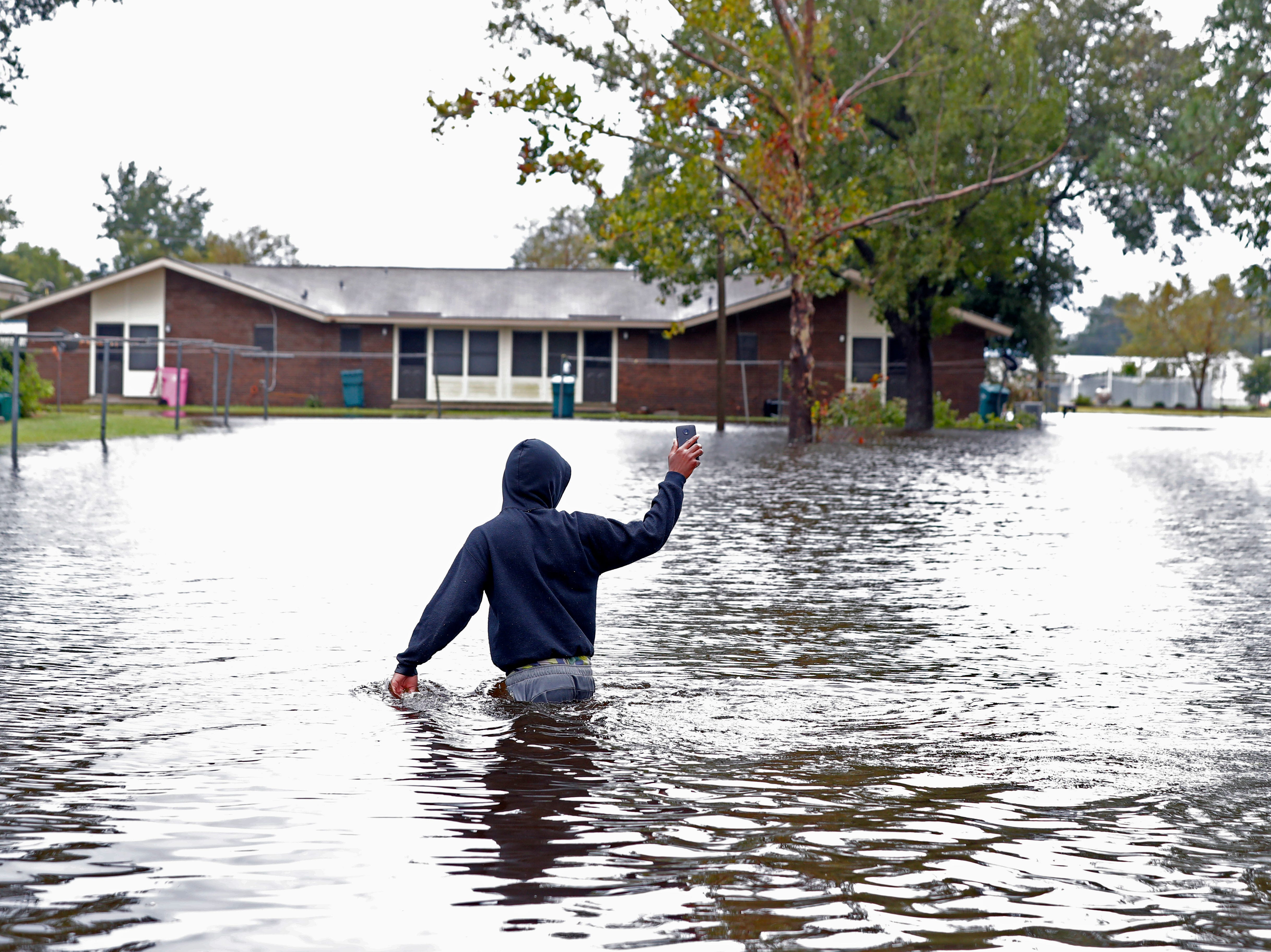 Camrey Mosley walks down a street through floodwaters from Hurricane Florence, in Marion, S.C., Sunday, Sept. 16, 2018.