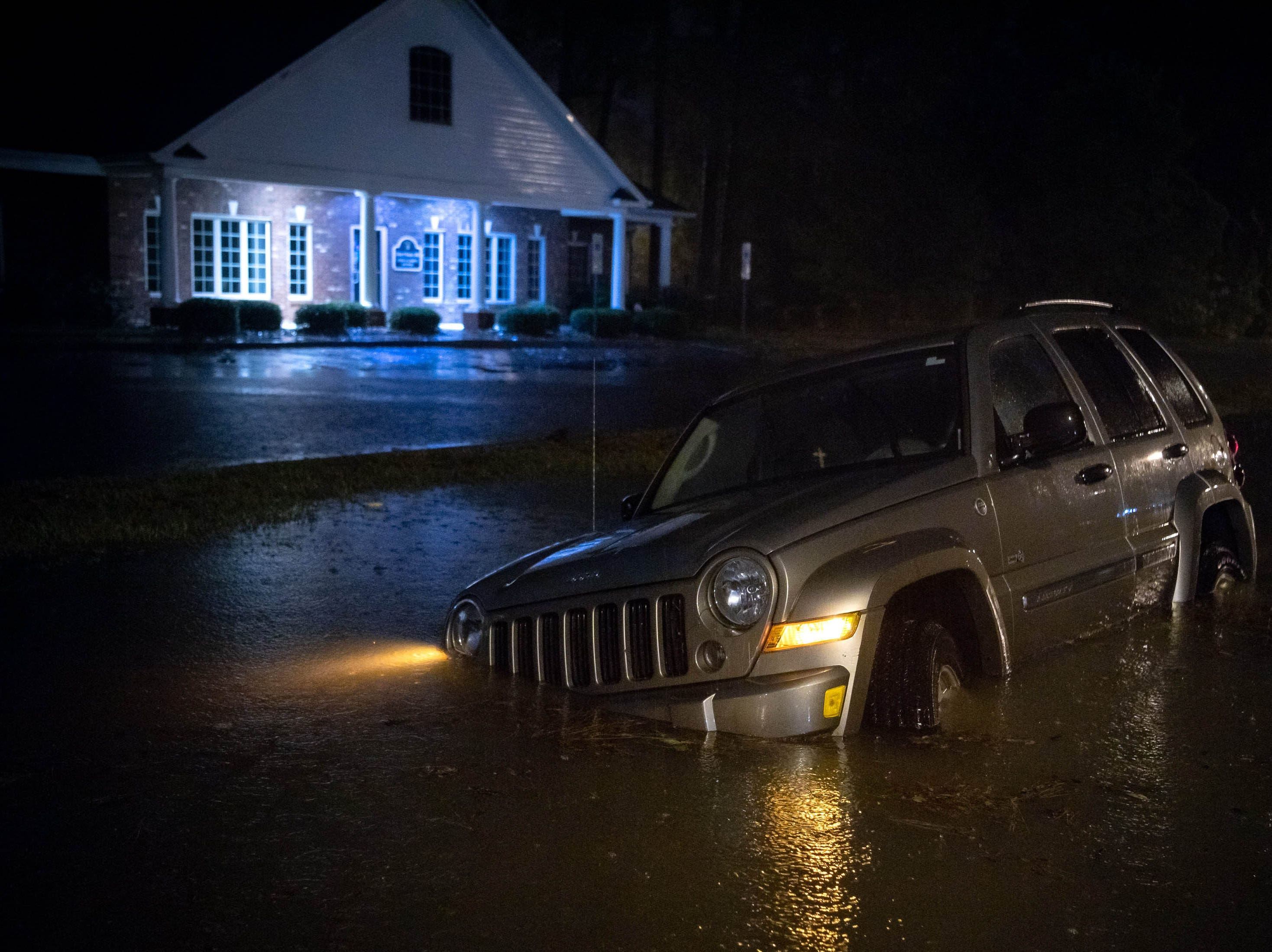 Sep 15, 2018; Lumberton, NC, USA; An abandoned SUV sits in a flooded neighborhood as rain from Tropical Storm Florence continues to fall on Lumberton, N.C., Saturday, Sept. 15, 2018.