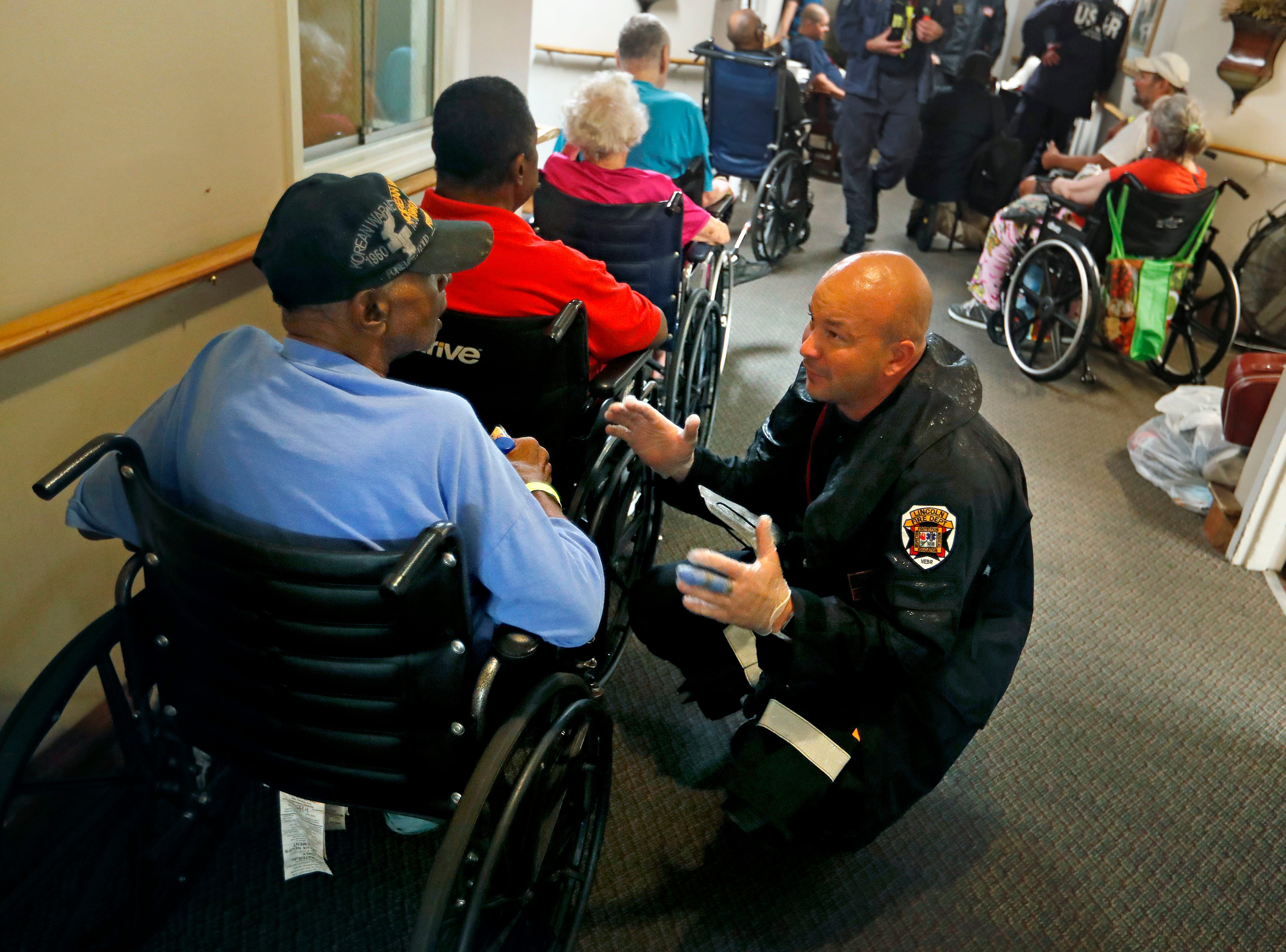 Mathew Meyer of the Nebraska Task Force 1 urban search and rescue team, right, talks with Korea war veteran Roman Wiggs, 87, as they evacuate an assisted living facility to a church as a precaution against potential flooding the city could see from tropical storm Florence in Fayetteville, N.C., Saturday, Sept. 15, 2018.