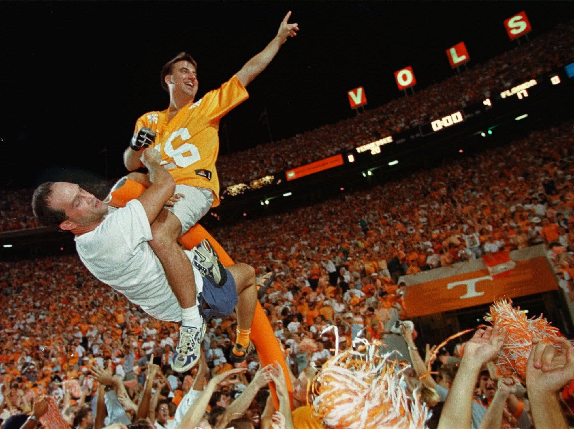 A fan wearing a Peyton Manning jersey sits on top of what is left of a goalpost as Tennessee fans take over the playing field after the Volunteers defeated Florida 20-17 in overtime in Knoxville, Tenn, on Saturday, Sept. 19, 1998. Florida had beaten Tennessee for the previous five years.