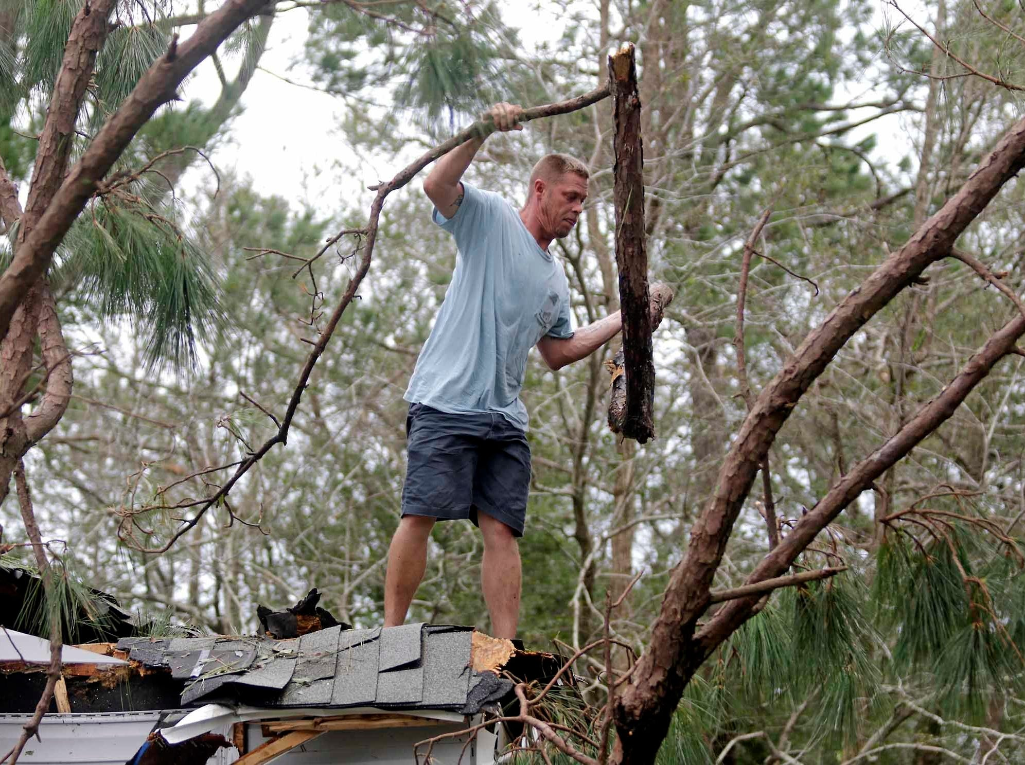 Chris Lishka works to remove a tree from his roof after Hurricane Florence hit Emerald Isle N.C., Sunday, Sept. 16, 2018.