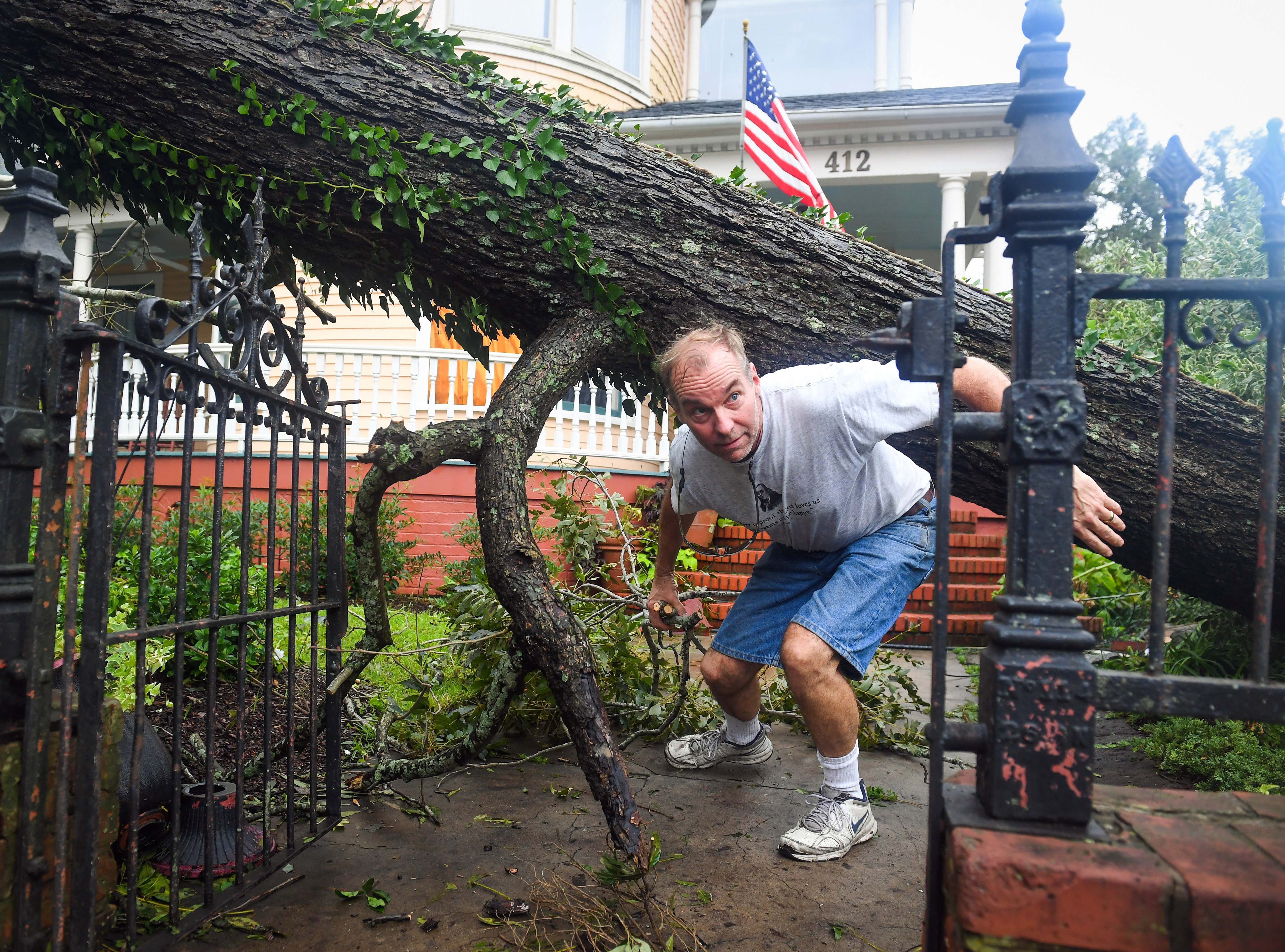 Sept 16, 2018; Charleston, SC, USA; Doug Erickson begins the task of cleaning the large fallen pecan tree in front of the CW Worth House in historic Wilmington, NC.