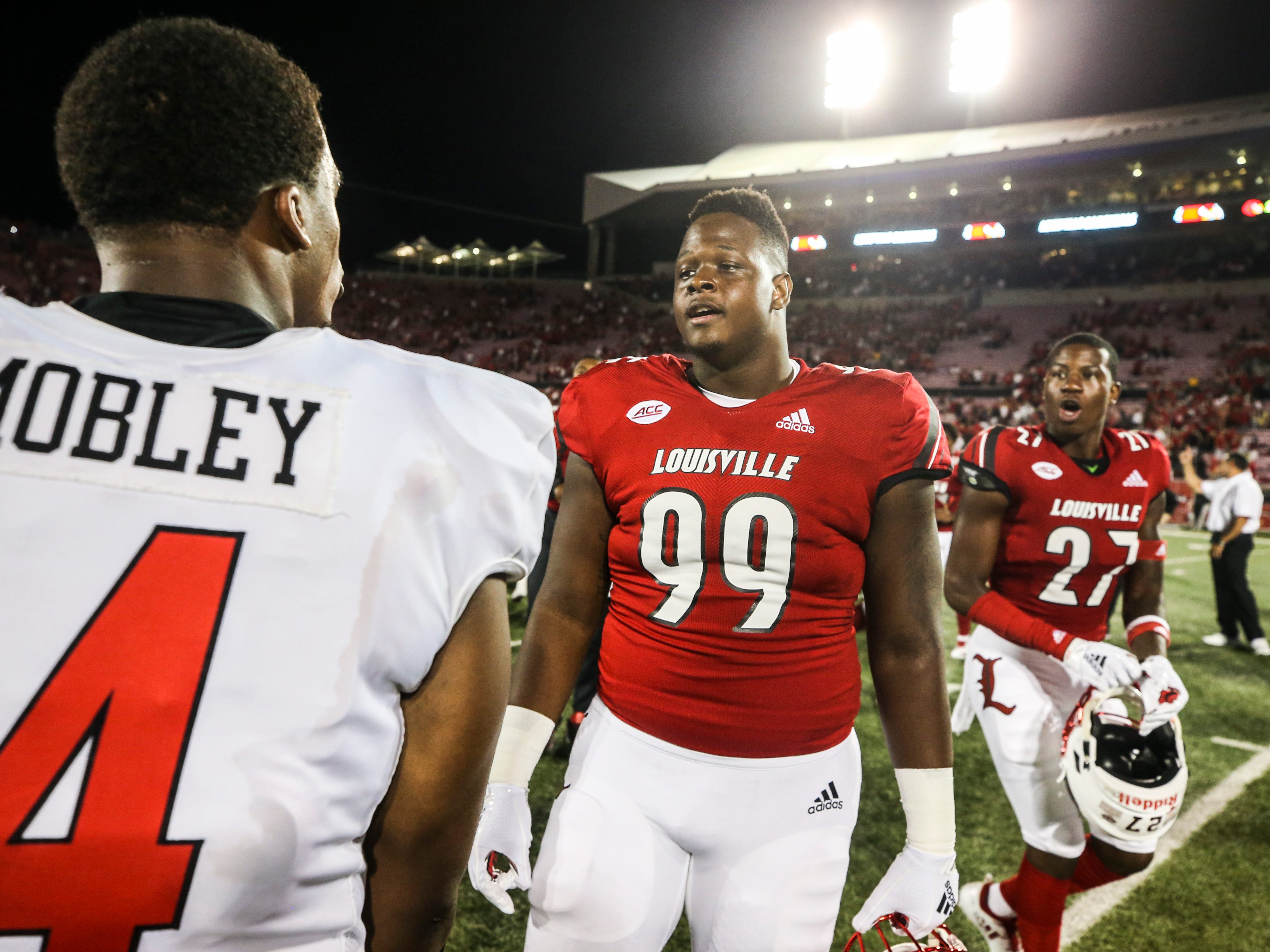 Louisville's Allen Love and Western Kentucky's Der'Quione Mobley exchange words after the Cardinals finally defeated the Hilltoppers 20-17 Saturday, Sept. 15, 2018.