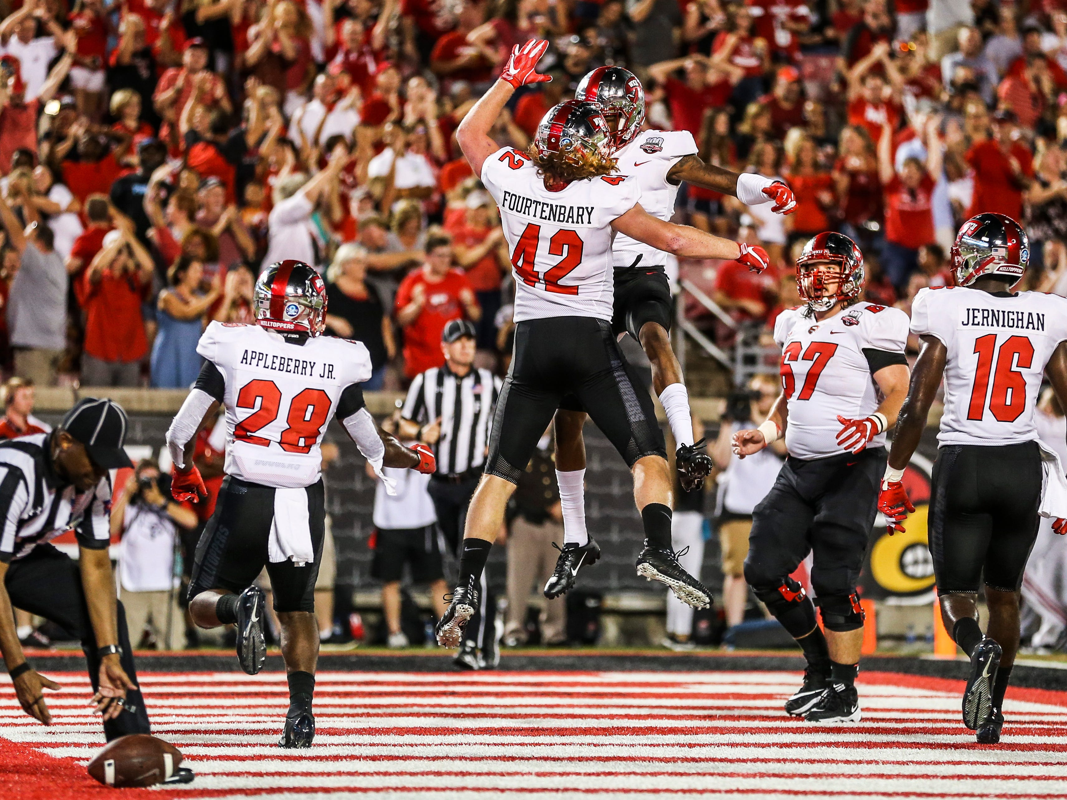 Western Kentucky's Kyle Fourtenbary celebrates his rushing touchdown with his teammates after scoring against Louisville to put the Toppers up 7-0 in the first half Saturday, Sept. 15, 2018.
