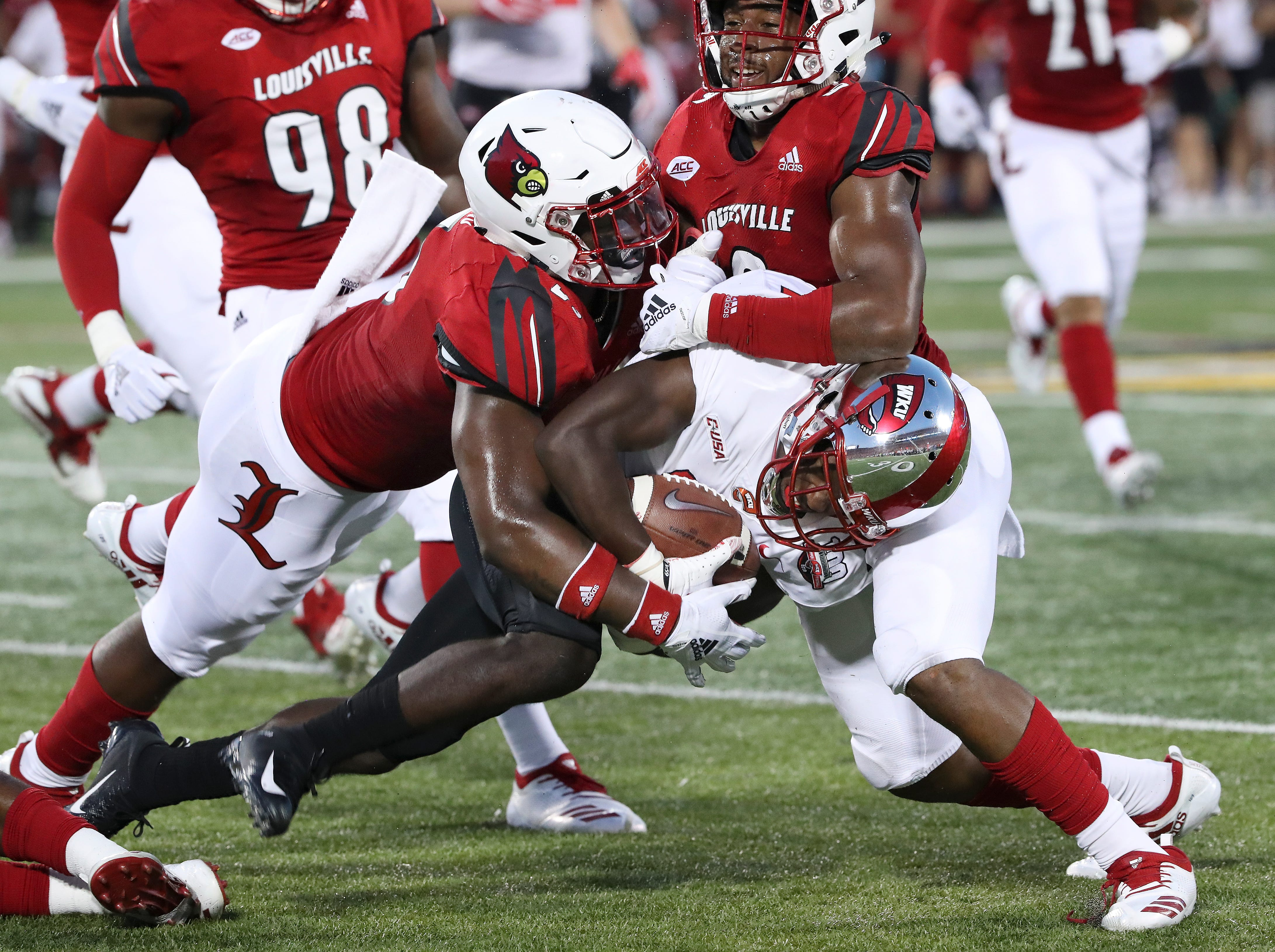 WKU's Garland LaFrance (14) tried squeeze out a few extra yards against Louisville's Robert Hicks (5) and C.J. Avery (9) during their game at Cardinal Stadium.