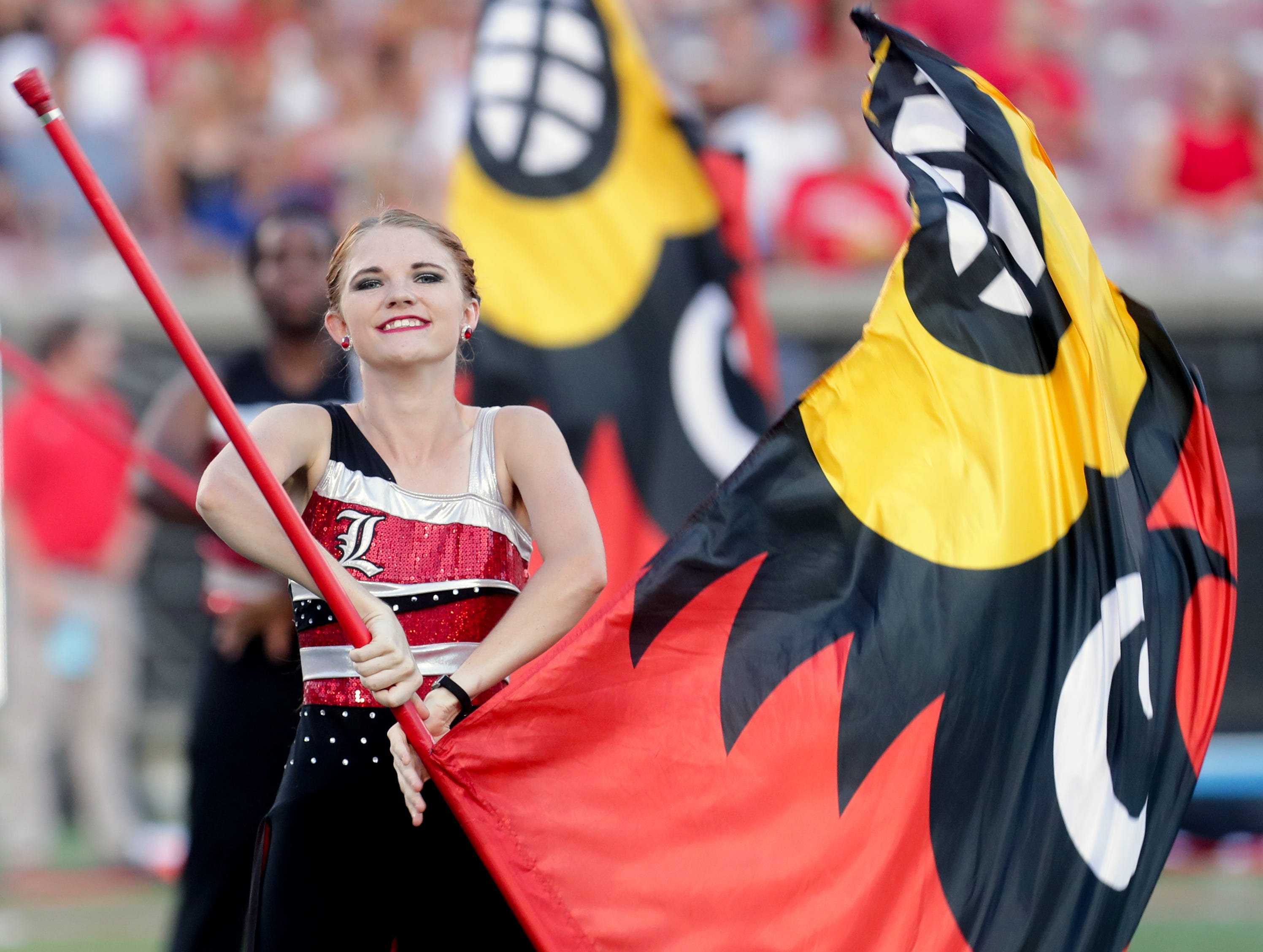 The  Louisville Marching Band Color Guard performs before the game against WKU. 