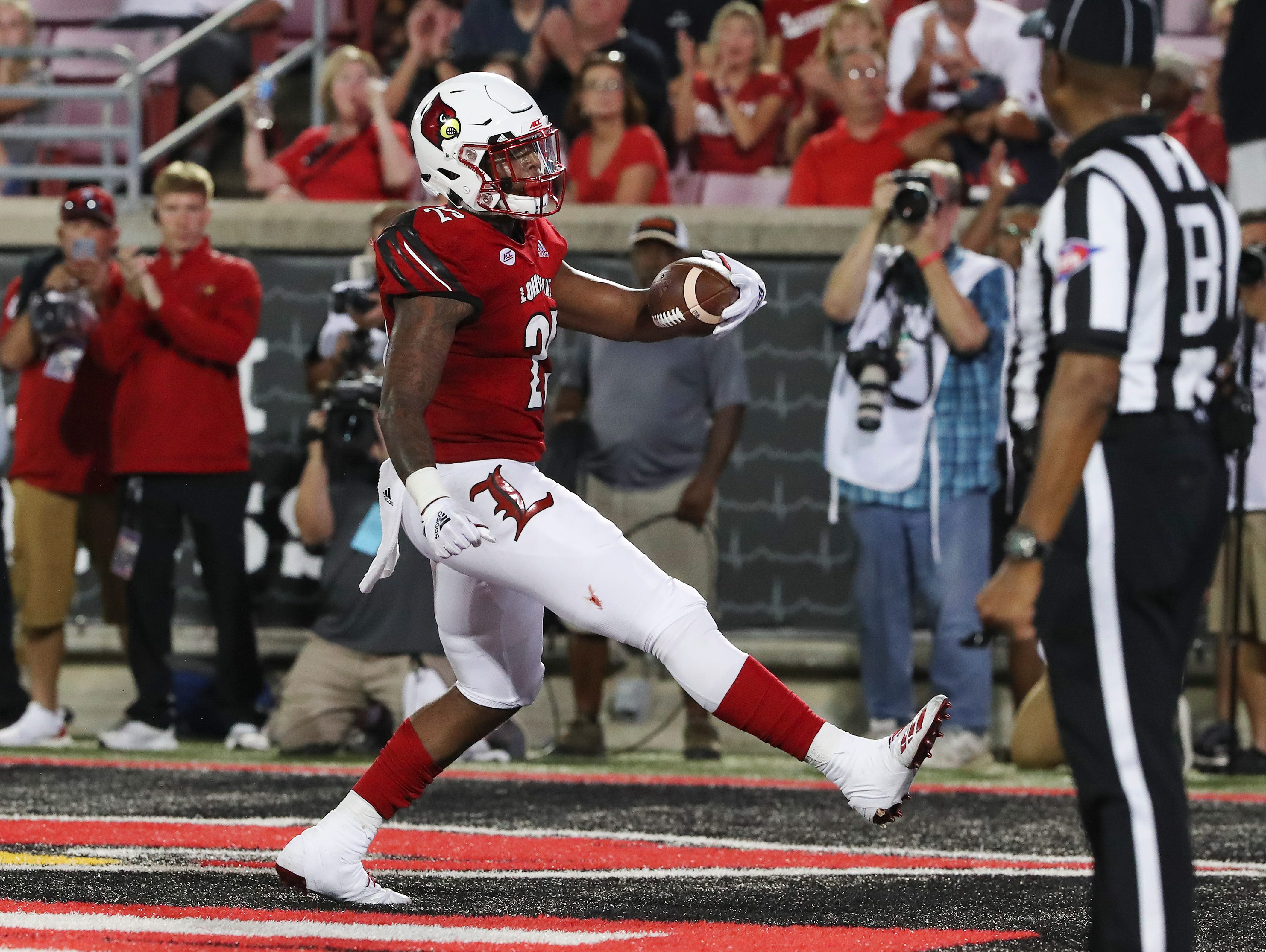 Louisville's Dae Williams (25) celebrates in the endzone as he scored a touchdown to take a 20-17 lead against WKU during their game at Cardinal Stadium.
