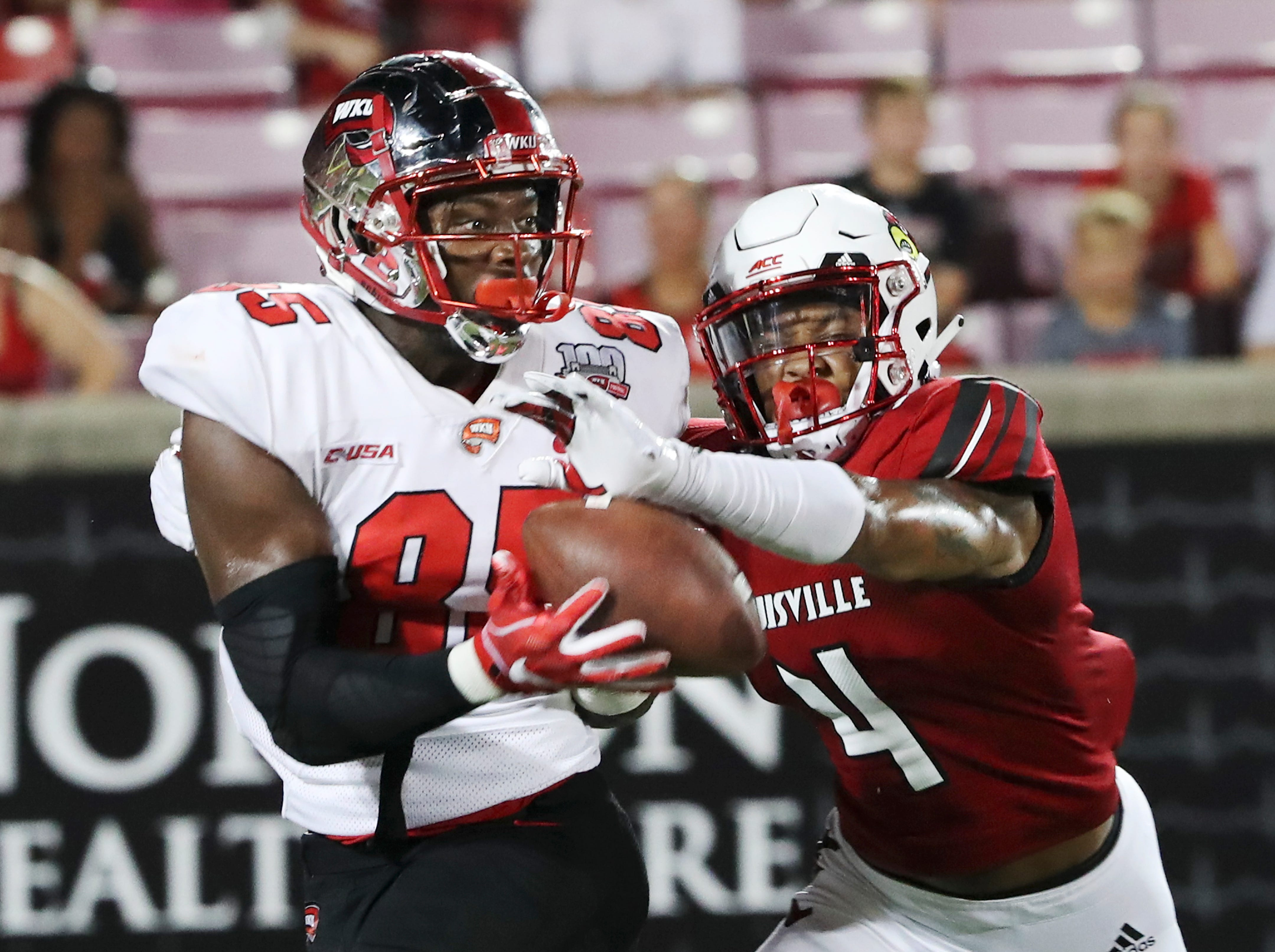 Louisville's TreSean Smith (4) breaks up a pass play in the endzone against WKU's Mik'Quan Deane (85) during their game at Cardinal Stadium.
