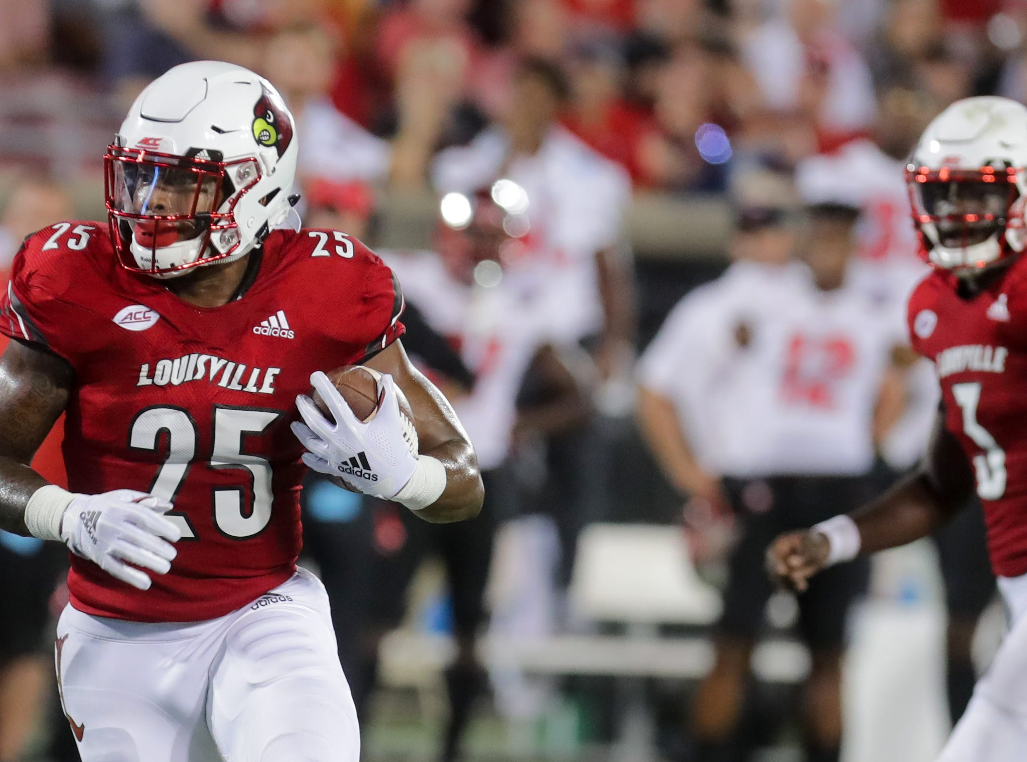 Louisville's Malik Cunningham, right, watches Dae Williams find some light and enough yards to get them just shy of the goal line.  