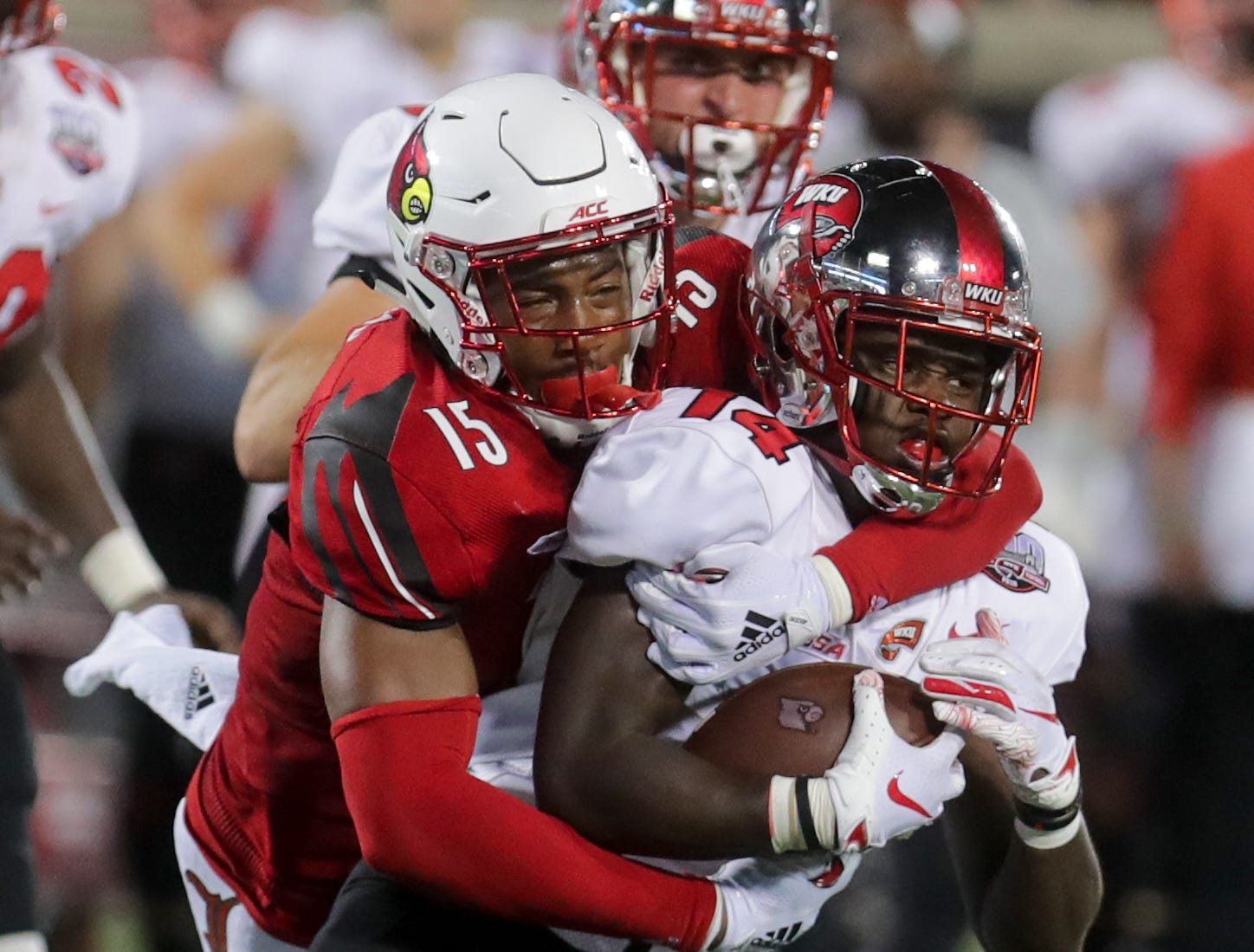 Louisville's Quen Head tackles WKU's Garland LaFrance for a loss. 