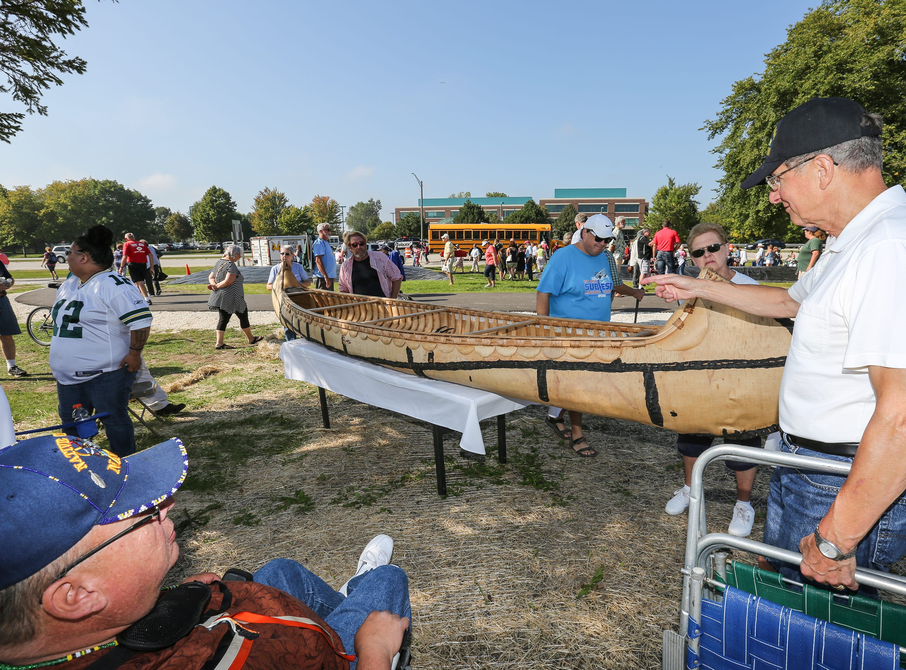 The public checks out a real birch bark canoe during the Spirit of the Rivers monument dedication Sunday, Sept. 16, 2018, in Two Rivers, Wis.