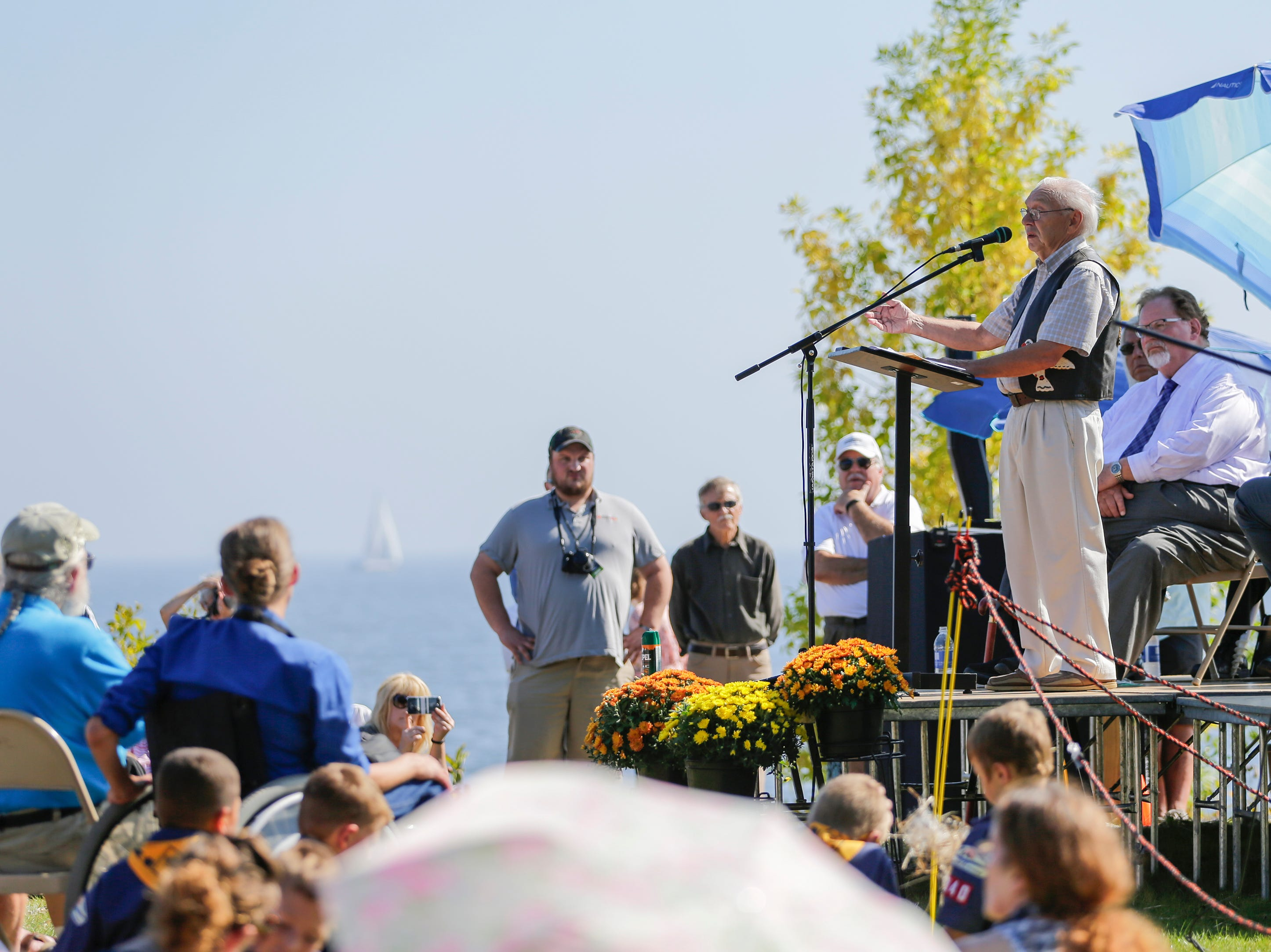"""Artist R.T. """"Skip"""" Wallen speaks during the Spirit of the Rivers monument dedication Sunday, Sept. 16, 2018, in Two Rivers, Wis."""