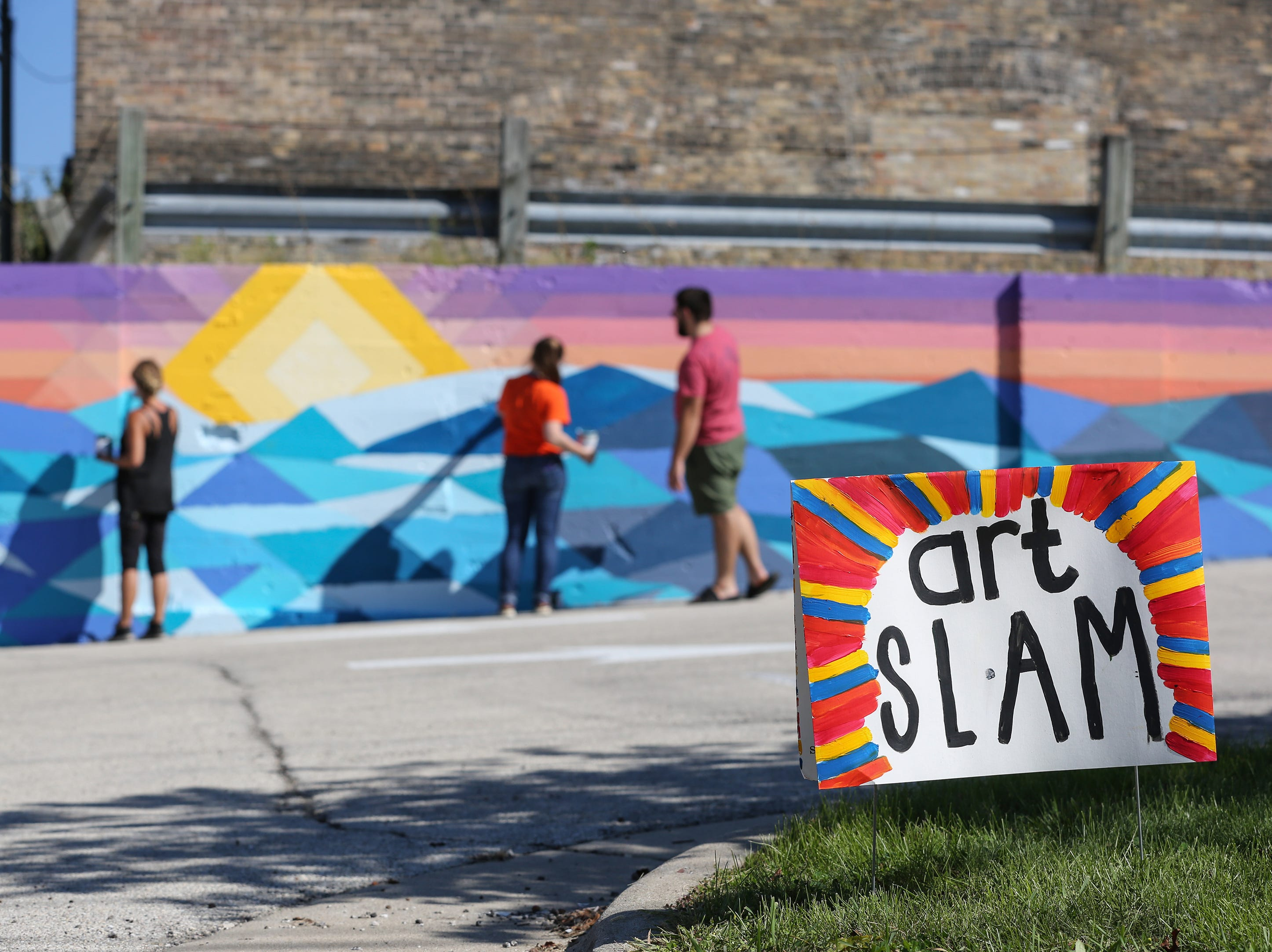 People work on the public mural project during Art Slam Saturday, September 15, 2018, in Manitowoc, Wis. The public was invited to fill in a square of the paint-by-numbers mural at 9th and Jay Street. Josh Clark/USA TODAY NETWORK-Wisconsin