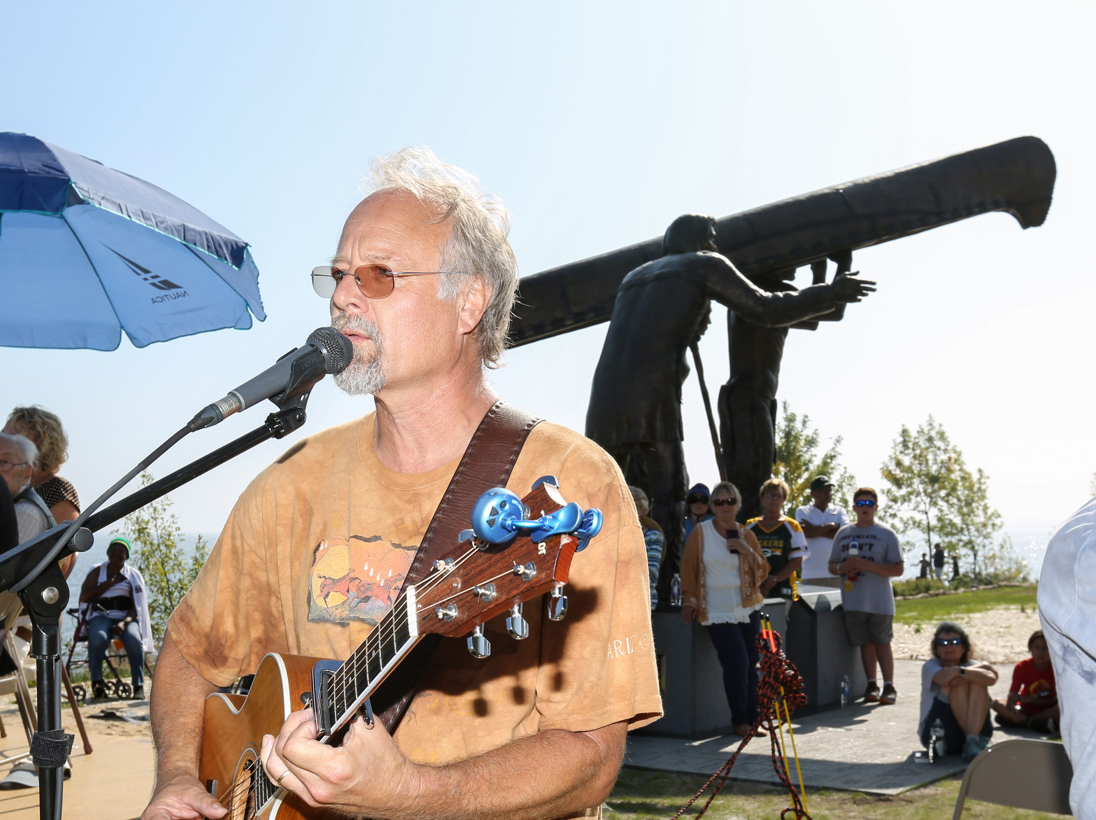 Pete Honzik sings and original song he wrote during the Spirit of the Rivers monument dedication Sunday, Sept. 16, 2018, in Two Rivers, Wis.