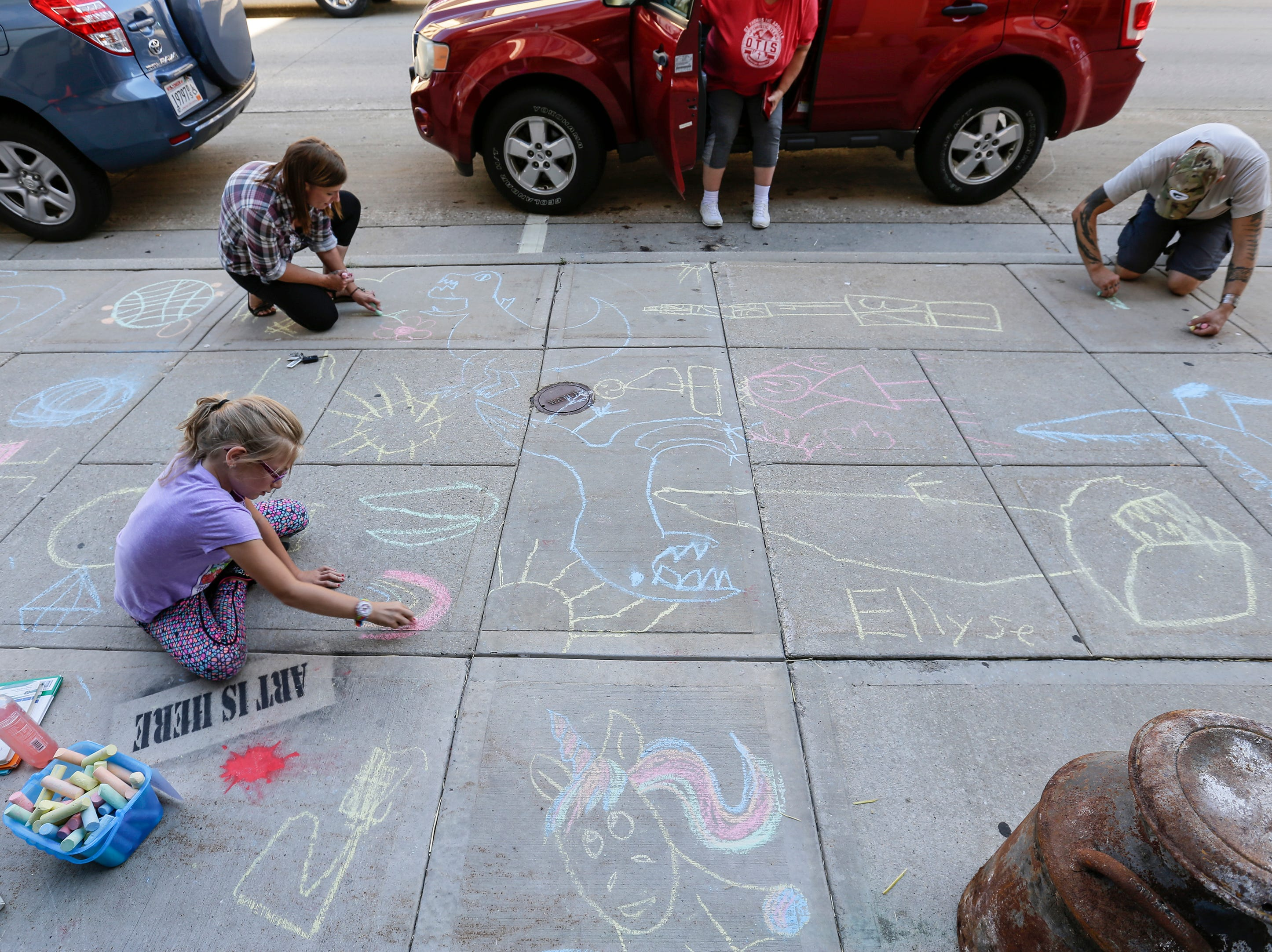 Makayla, 11, and her parents Becky and Eric Larsen color with sidewalk chalk outside Modern by Megan during the Art Slam Saturday, September 15, 2018, in Manitowoc, Wis. Josh Clark/USA TODAY NETWORK-Wisconsin