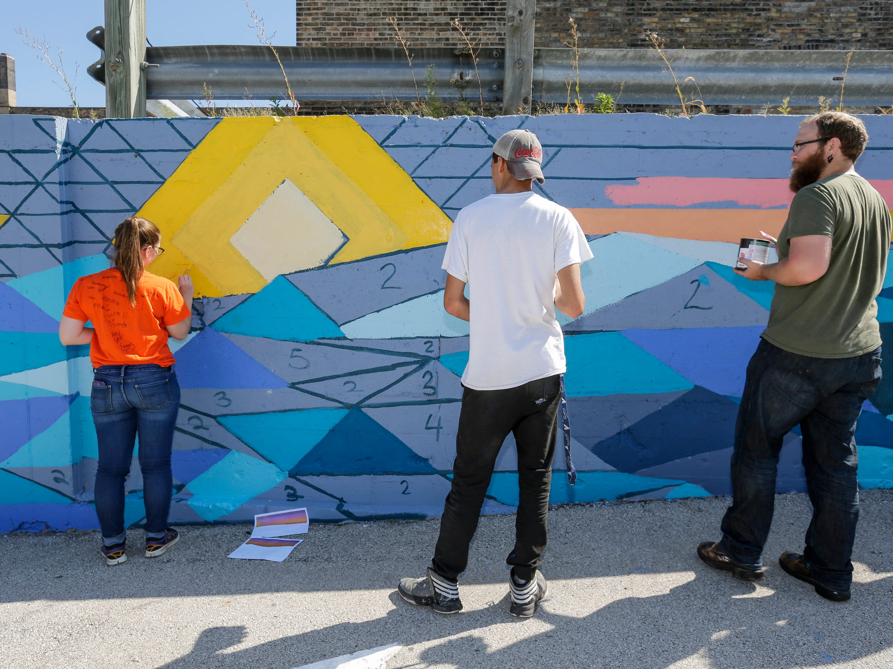 People work on a public mural during Art Slam Saturday, September 15, 2018, in Manitowoc, Wis. The public was invited to fill in a square of the paint-by-numbers mural at 9th and Jay Street. Josh Clark/USA TODAY NETWORK-Wisconsin