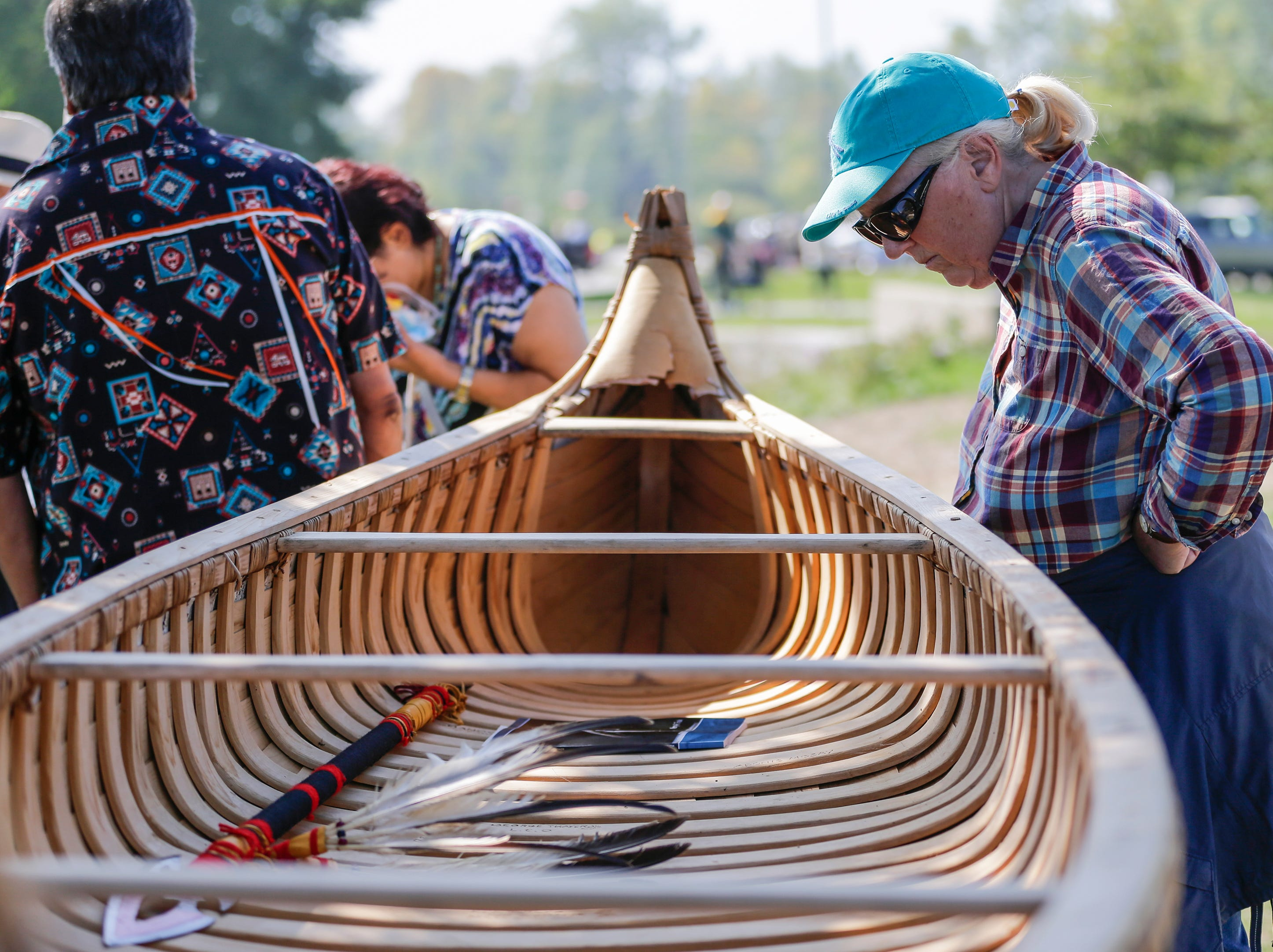 Janis King of Manitowoc takes a closer look at the birch bark canoe on display during the Spirit of the Rivers monument dedication Sunday, Sept. 16, 2018, in Two Rivers, Wis.