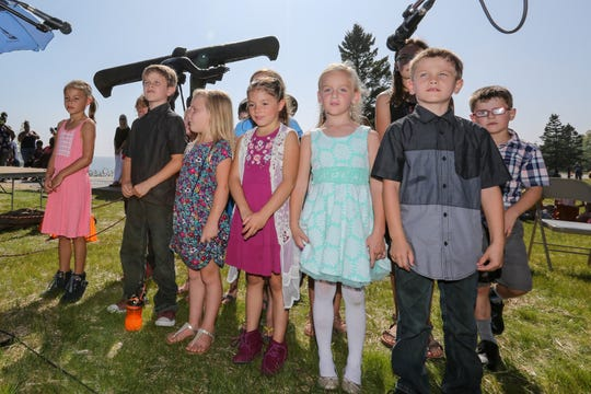 "Manitowoc public school children sing ""Spirit of the River,"" a song written by their music teacher David Bourgeois, during the Spirit of the Rivers monument dedication Sunday, Sept. 16, 2018, in Two Rivers, Wis."