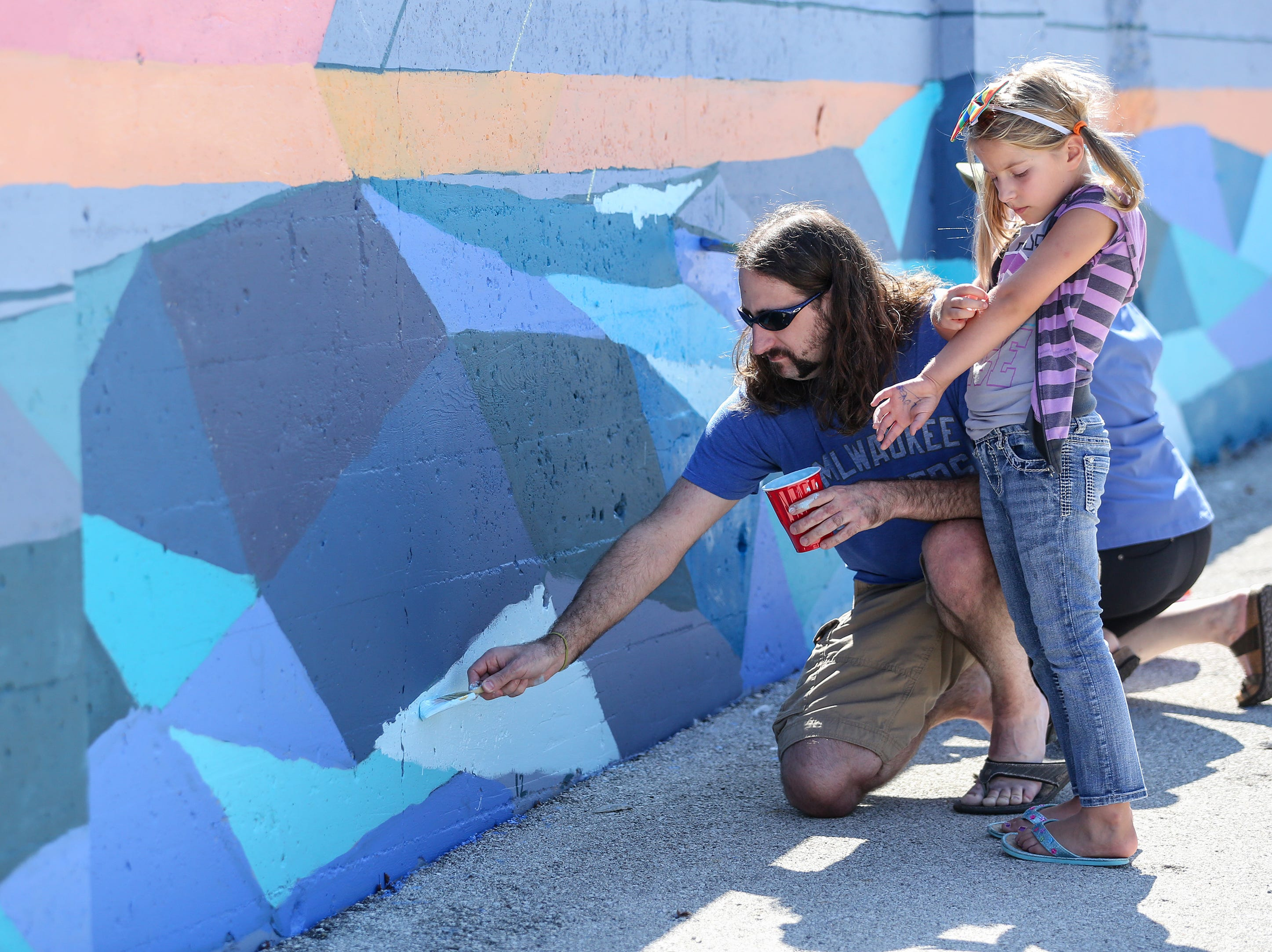 Brian his daughter Paige Mittnacht work on the public mural project during Art Slam Saturday, September 15, 2018, in Manitowoc, Wis. Josh Clark/USA TODAY NETWORK-Wisconsin