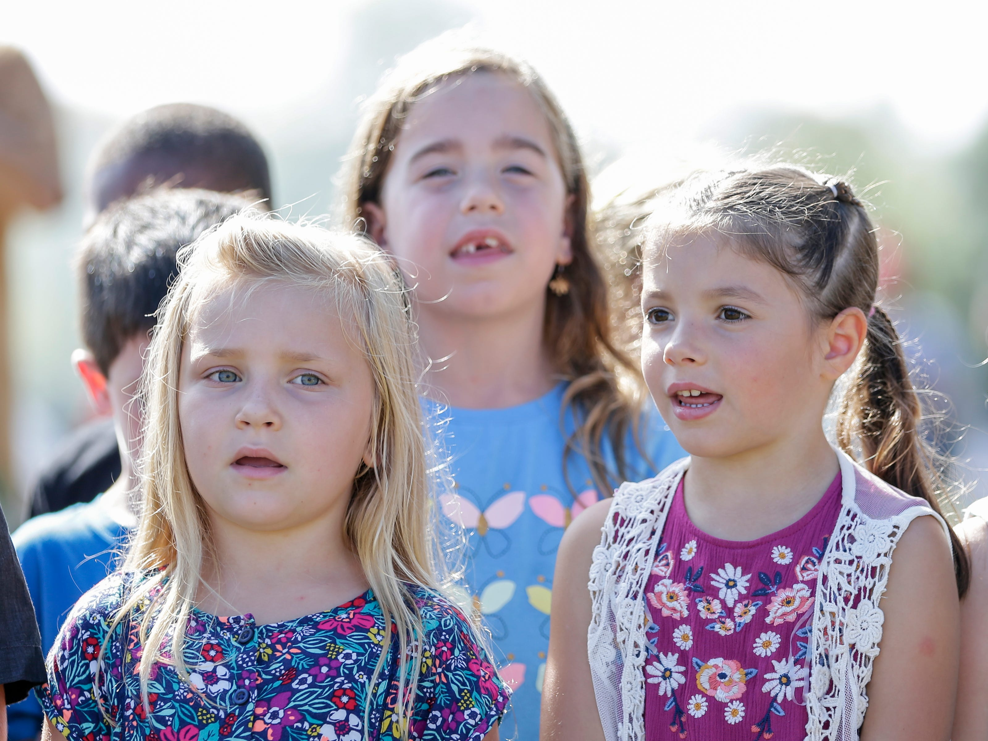 """Manitowoc public school children sing """"Spirit of the River,"""" a song written by their music teacher David Bourgeois, during the Spirit of the Rivers monument dedication Sunday, Sept. 16, 2018, in Two Rivers, Wis."""