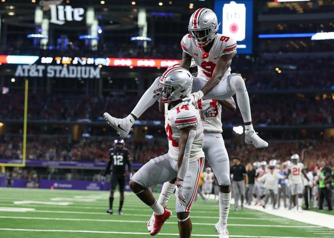 Ohio State H-back K.J. Hill (14) celebrates his third quarter touchdown with receiver Binjimen Victor in Saturday's 40-28 comeback win over TCU.
