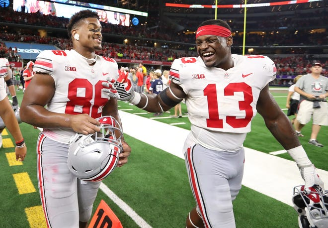 Defensive tackle Dre'Mont Jones (86), one of the heroes in Saturday's rally past TCU, celebrates the victory with tight end Rashod Berry.