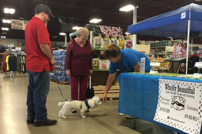 Alex Rockwell, his grandmother Ellie Rockwell and her 1.5-year-old French poodle Remy talk with Nan Coon, massage therapist at Wholly Beautiful Canine Massage Therapy and Grooming, during a Companion Pet event previously held at the Bucyrus Family Farm and Home Store.