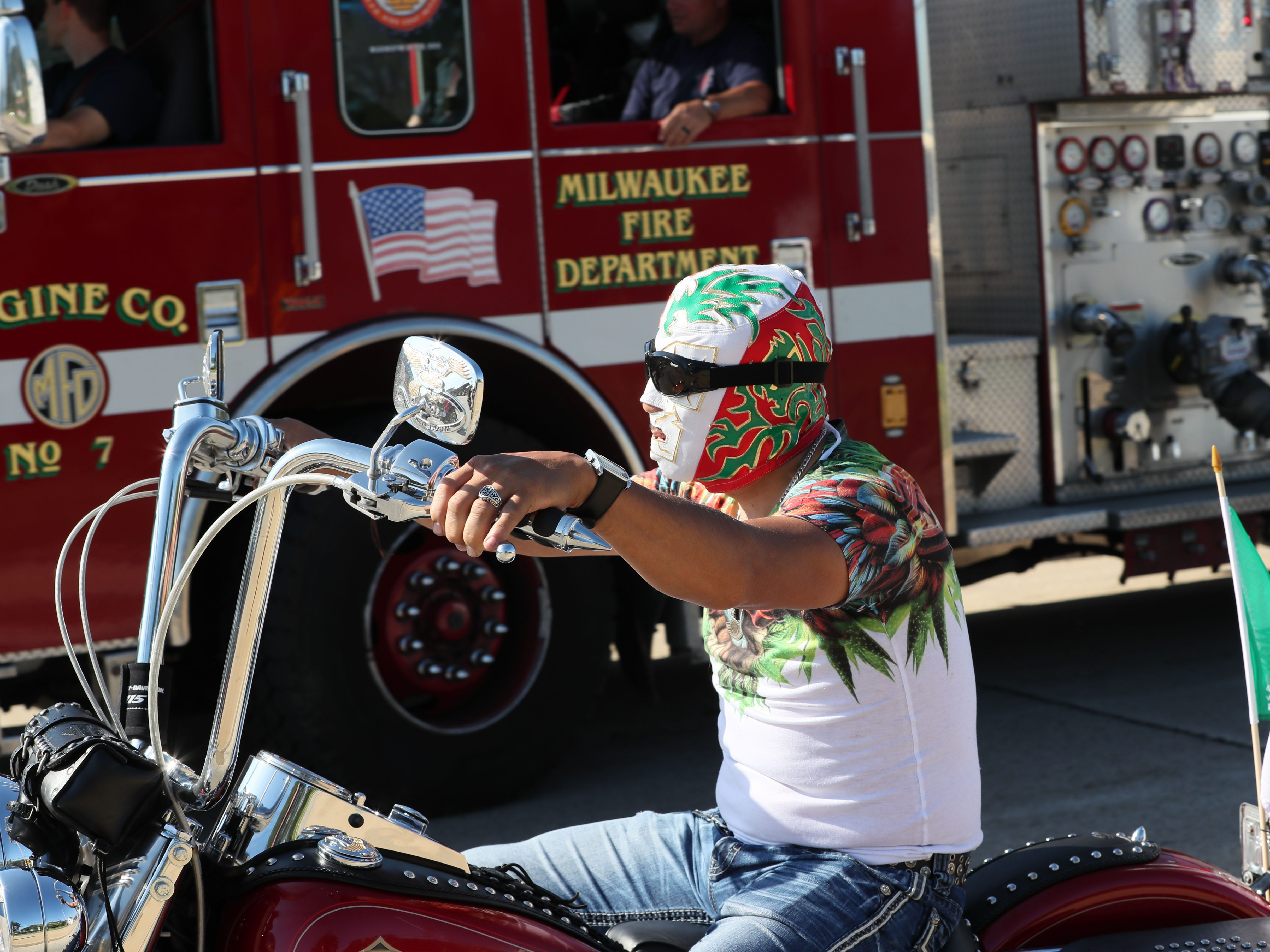 A motorcycle rider in the Mexican Independence Parade wears a brightly colored mask.