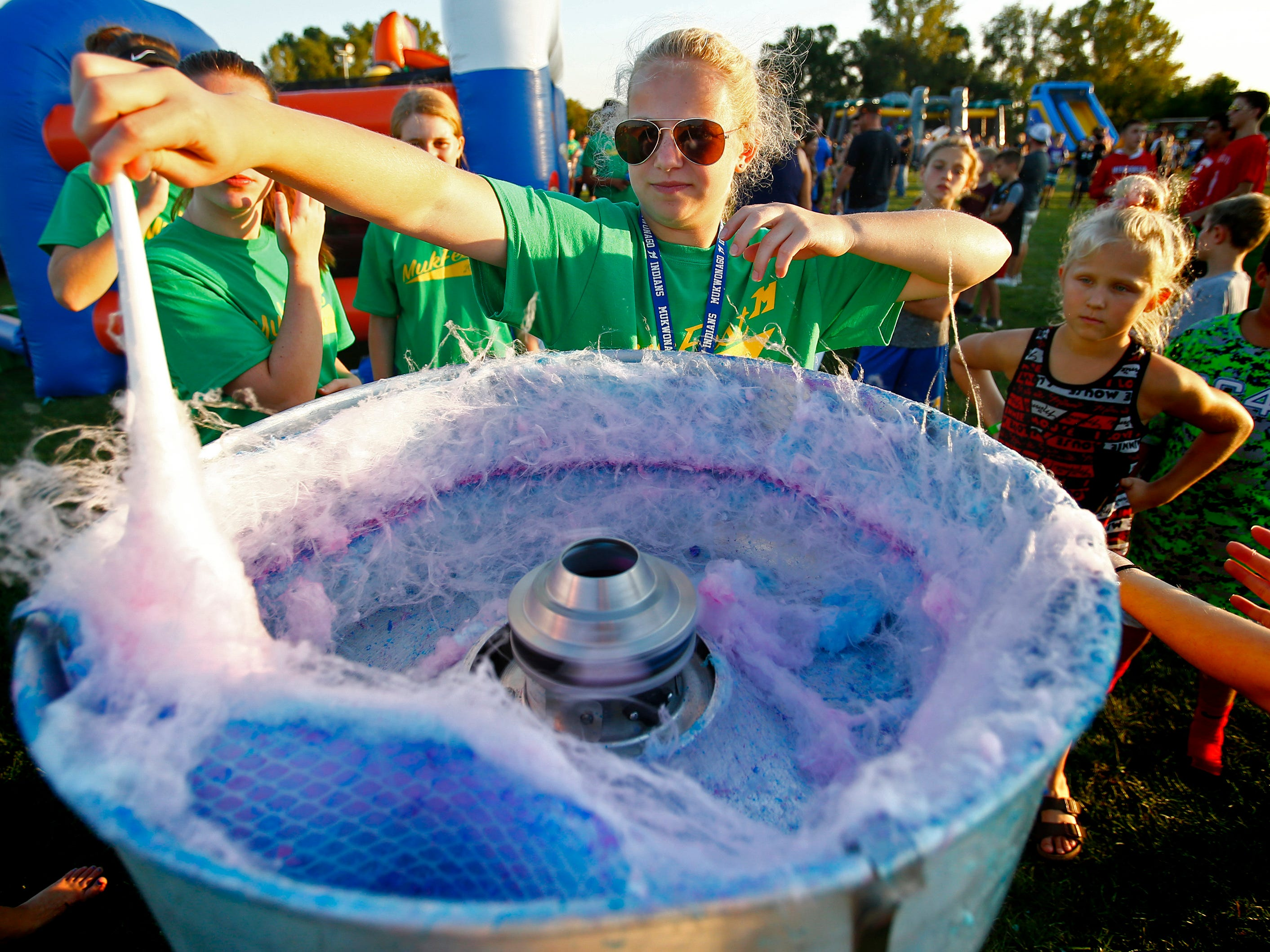 Kelly Muehlenkamp whirls up a cotton candy for a waiting child during Mukfest, presented by the Friends of Mukwonago Athletics, at Mukwonago High School on Sept. 14.