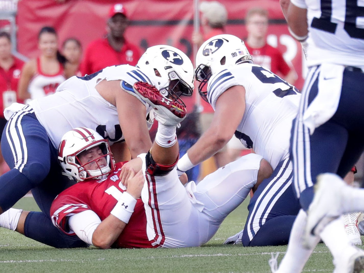 Wisconsin Badgers quarterback Alex Hornibrook is sacked by Brigham Young defensive lineman Uriah Leiataua (58) and defensive lineman Earl Tuioti-Mariner (91).