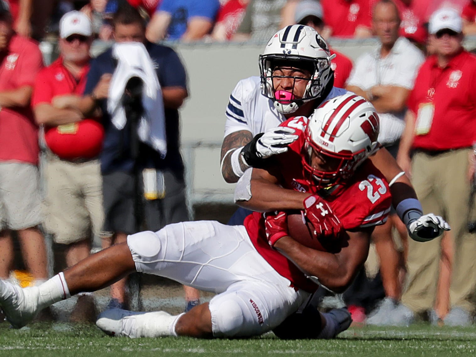 Wisconsin Badgers running back Jonathan Taylor is stopped for a loss by Brigham Young linebacker Sione Takitaki during the first half.