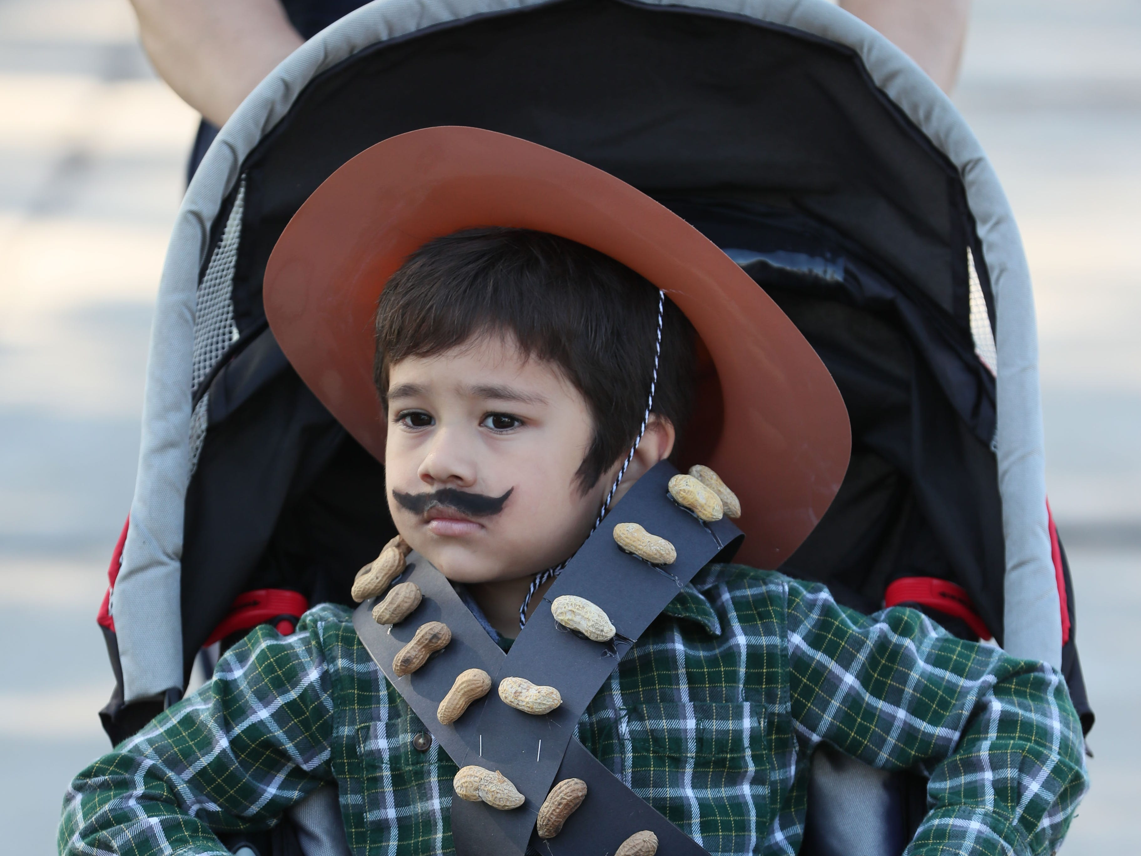 Fernando Navarro, 4, of Milwaukee rides to the parade in a costume recalling fighters for Mexican independence.
