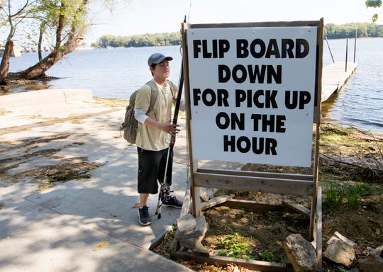 An angler flips down a sign for a ride to the Best Dam Fishing Float on the Mississippi River across from La Crosse.