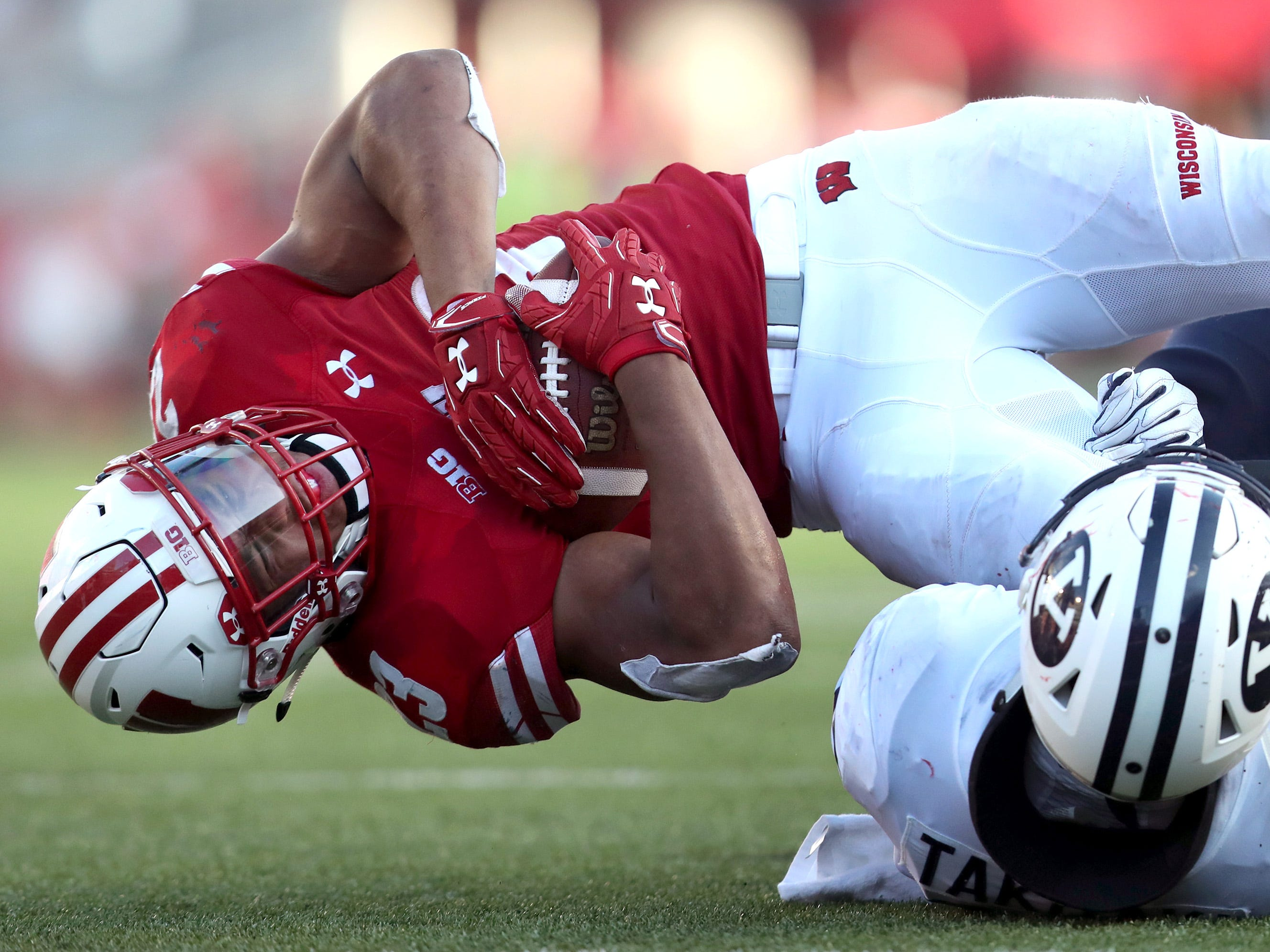 Wisconsin Badgers running back Jonathan Taylor is brought down by Brigham Young linebacker Sione Takitaki on Saturday.