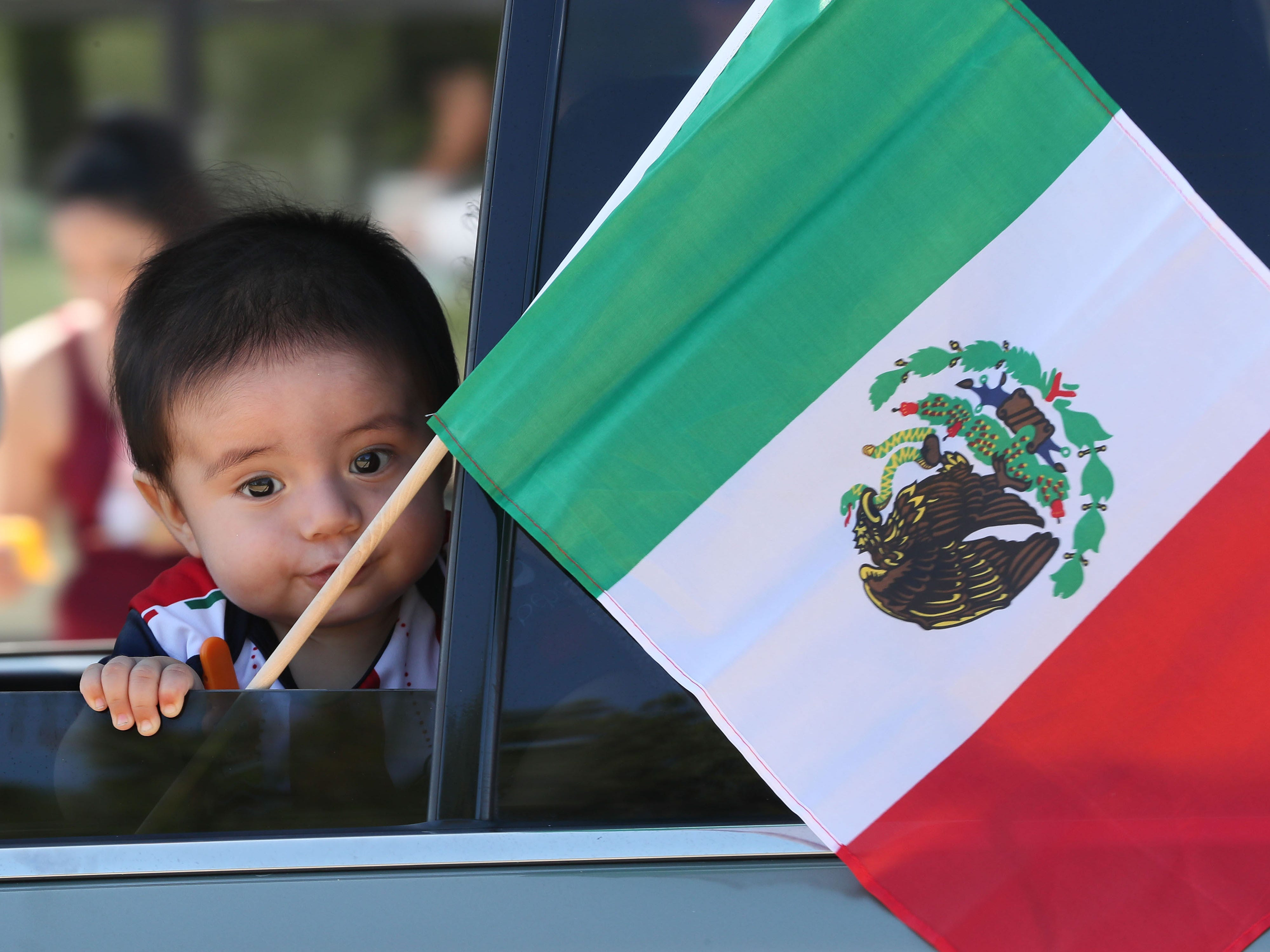 A young boy next to a Mexican flag looks out the window of a car during the independence parade.