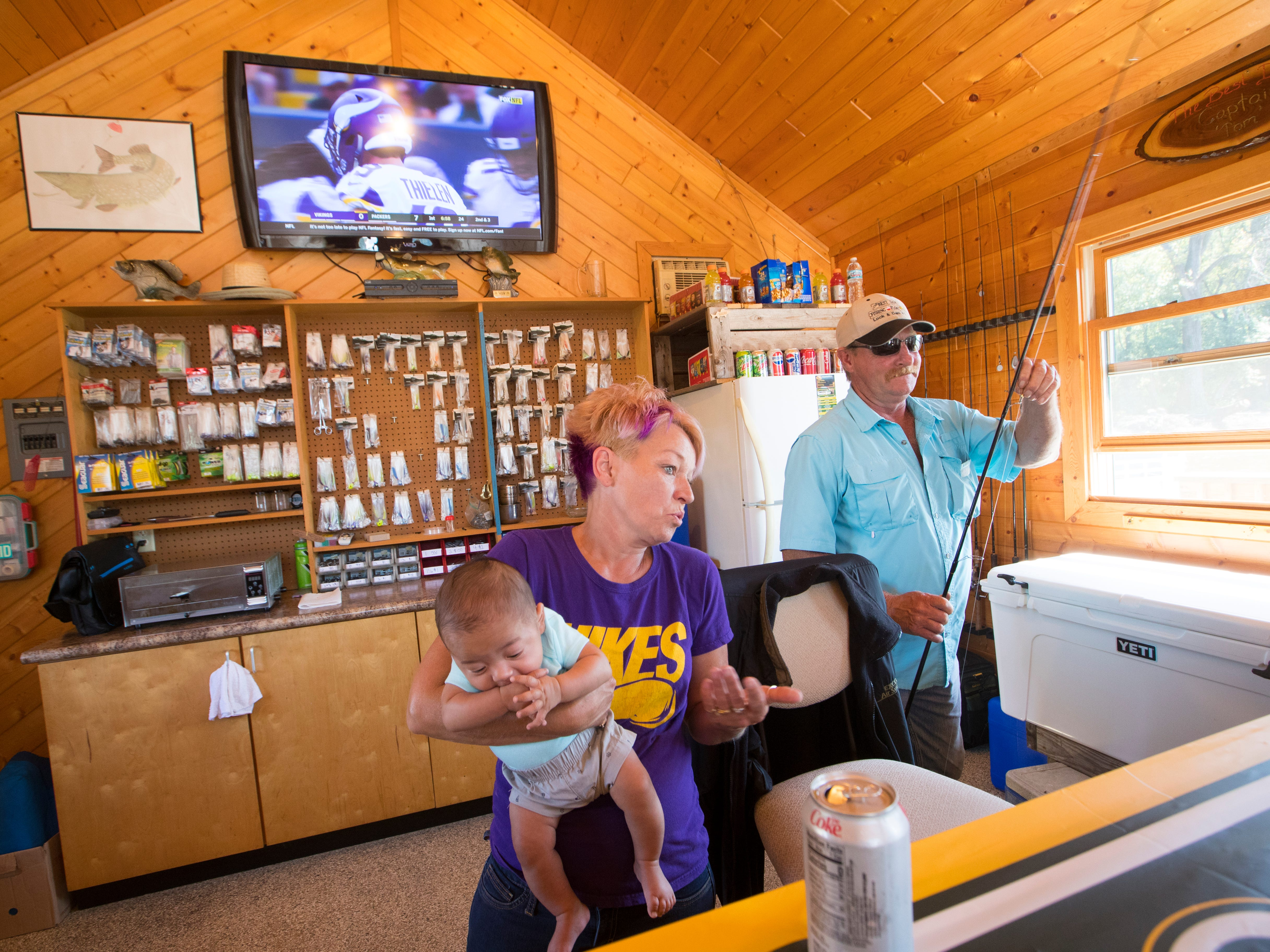 Julianna Rieple holds her 15-week-old grandson, Jayden Christiansen, while working behind the counter with her manager/husband, Tom, on Sunday aboard the Best Dam Fishing Float on the Mississippi River near La Crosse.