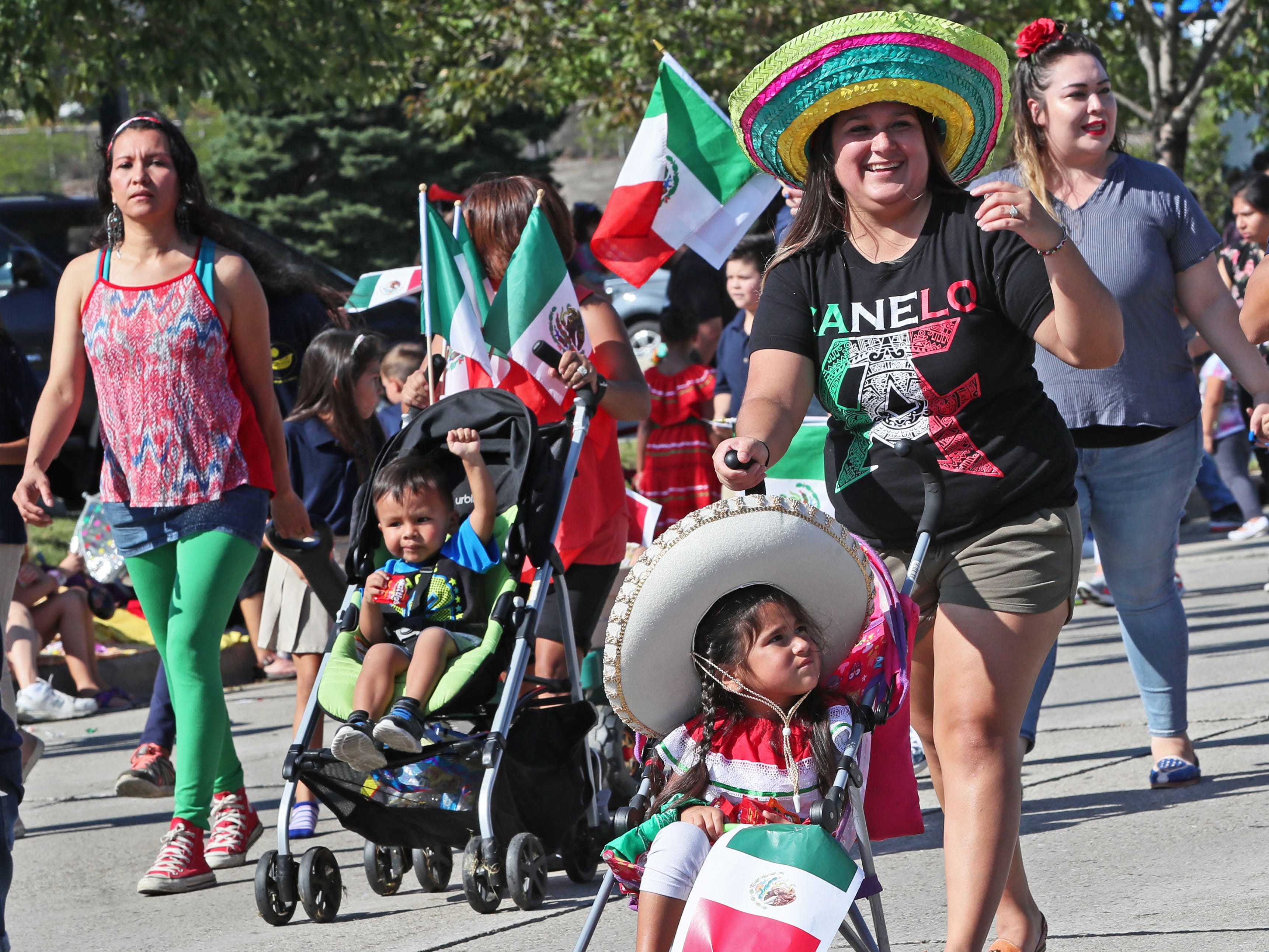 Vanessa Acosta of Milwaukee (right) pushes her daughter Alyna Martinez, 3, in a stroller while taking part in the parade with other parents and staff of St. Joseph Academy.