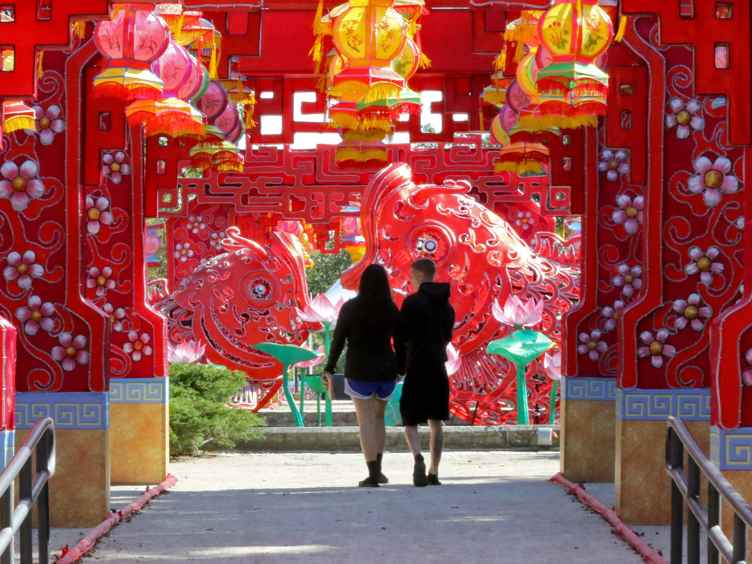 A couple walks through the main entrance to the China Lights display being assembled at the Boerner Botanical Gardens that is set to open Sept. 21. Full information on hours, dates and tickets can be found at www.chinalights.org.