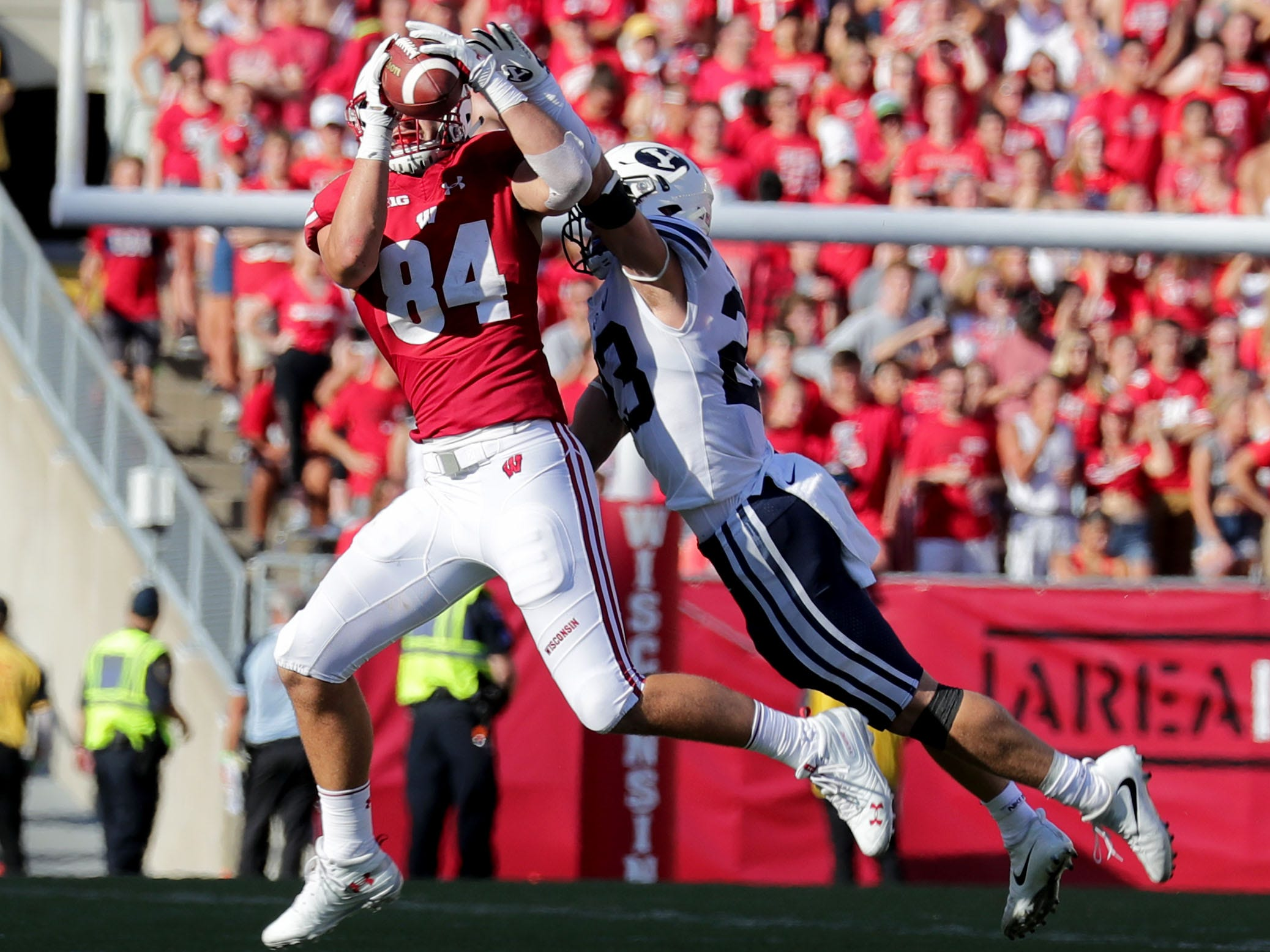 Wisconsin Badgers tight end Jake Ferguson catches a pass while defended by Brigham Young linebacker Zayne Anderson.