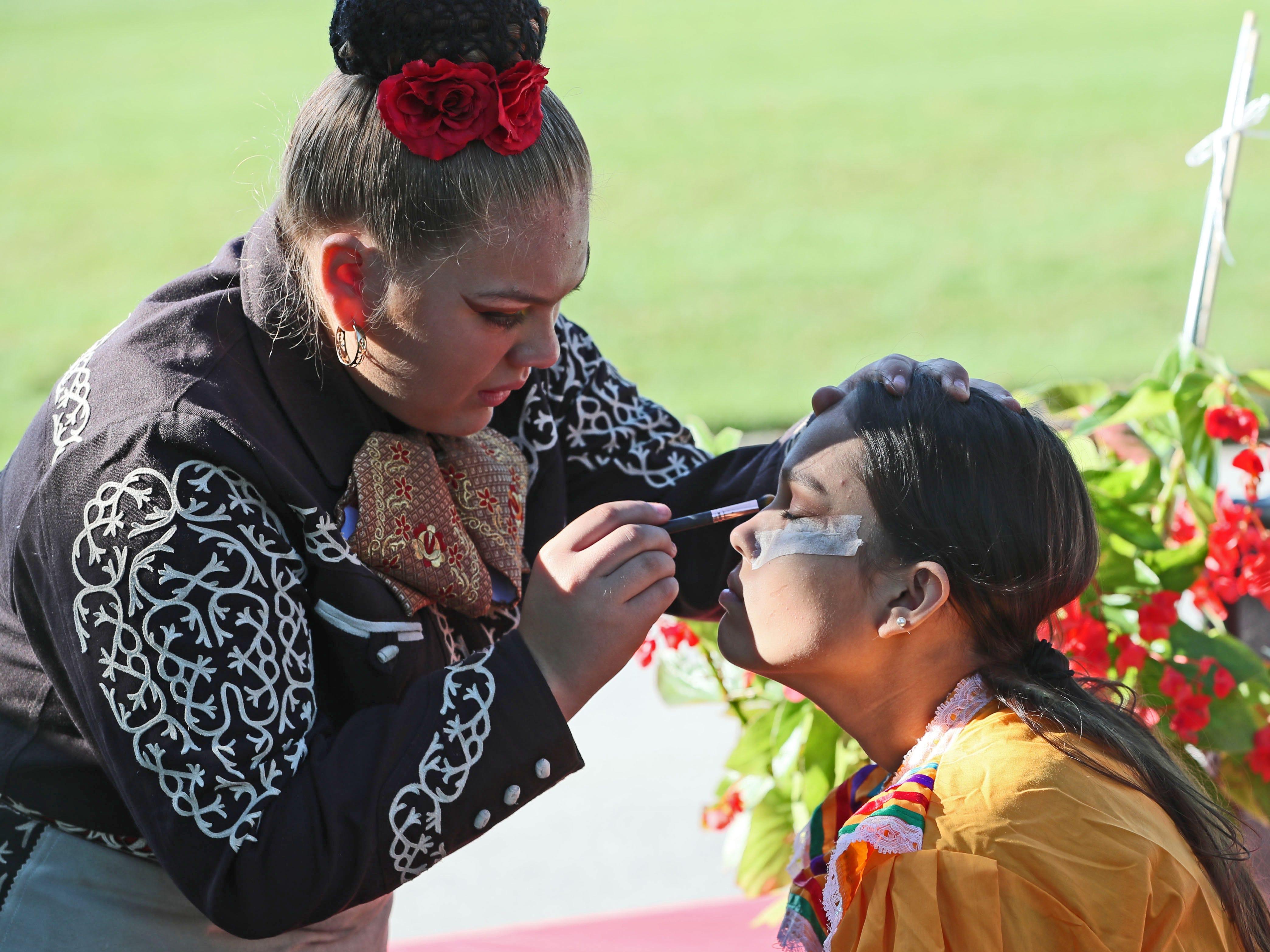 Alexandra Zuniga puts makeup on Yuritzia Gaona before the parade. Both are students at Morgandale School.