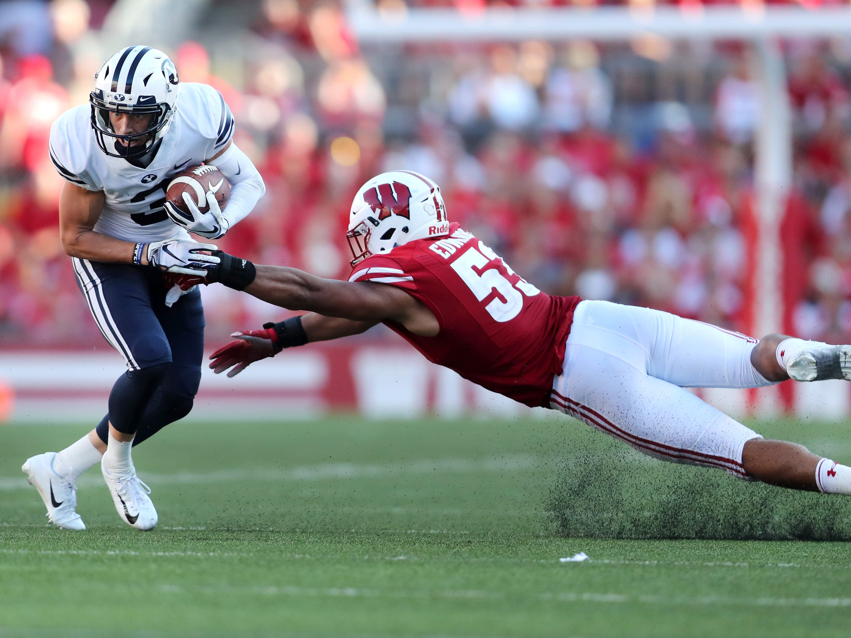 Wisconsin Badgers linebacker T.J. Edwards (53) slips as he tries to tackle Brigham Young wide receiver Dylan Collie.