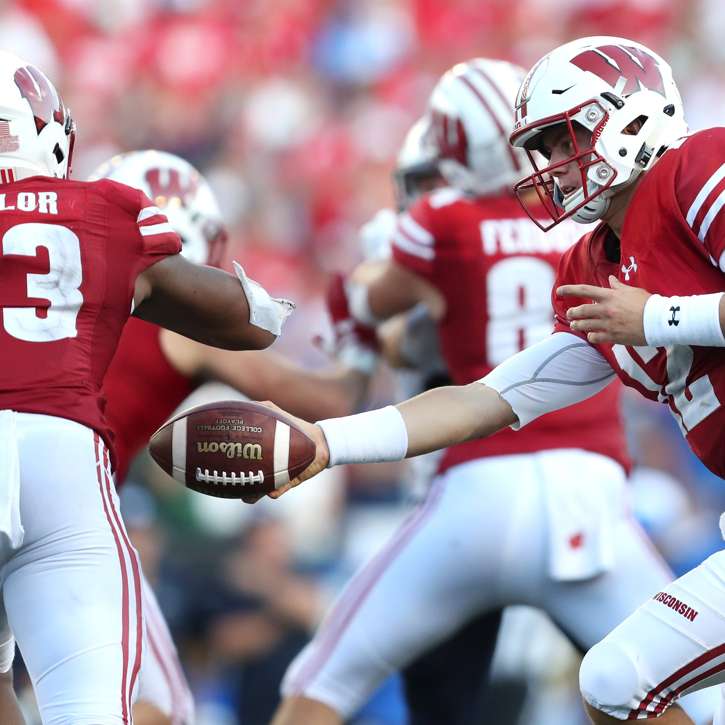 Wisconsin Badgers quarterback Alex Hornibrook hands the ball off to running back Jonathan Taylor.