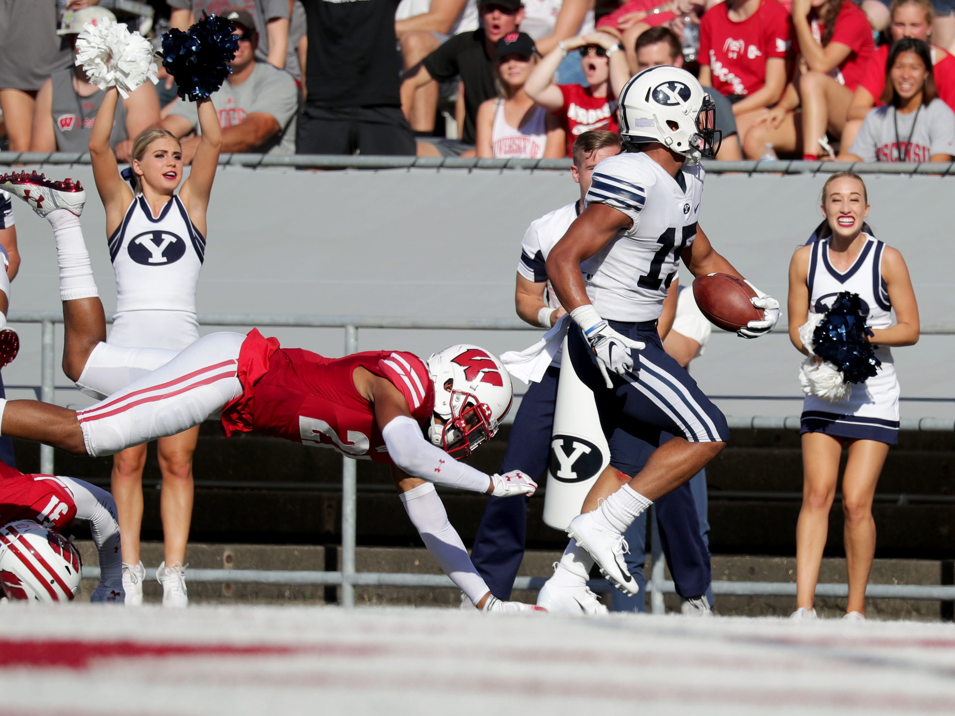 Brigham Young Cougars wide receiver Aleva Hifo runs after a catch as Wisconsin Badgers cornerback Caesar Williams tries to make a tackle.