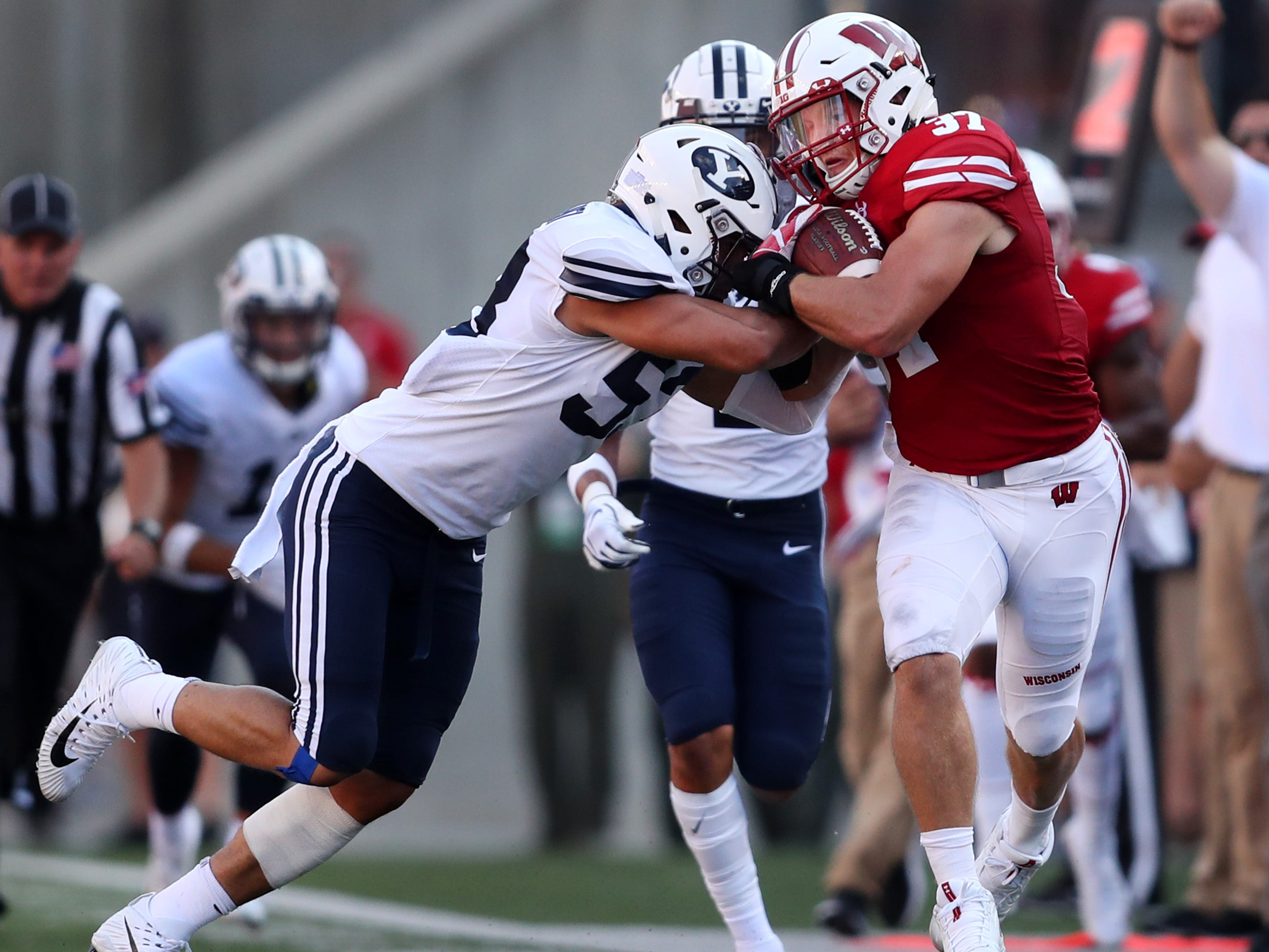 Wisconsin Badgers running back Garrett Groshek is pushed out of bounds by Brigham Young linebacker Isaiah Kaufusi on Saturday.
