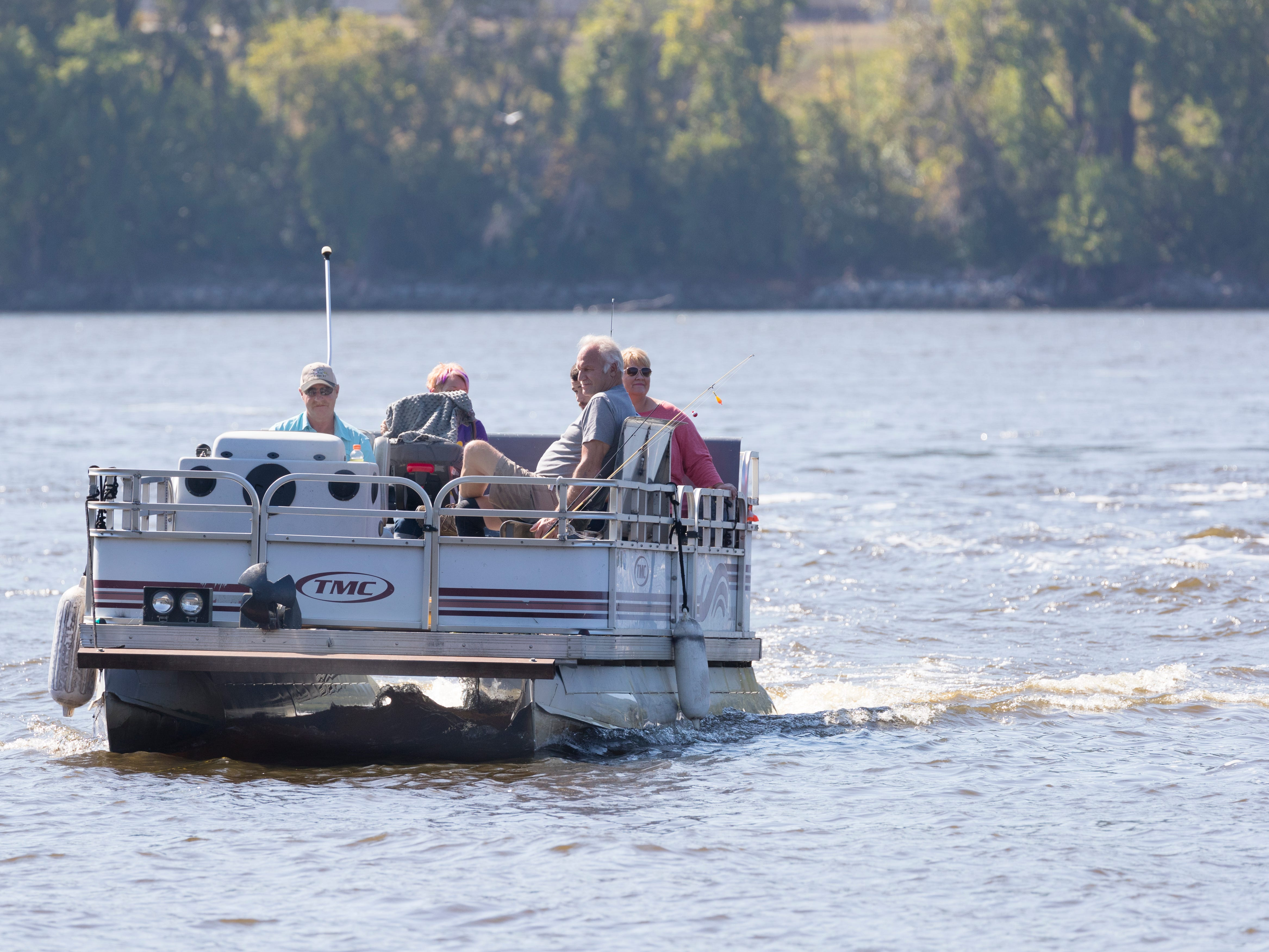 Tom Rieple is at the helm of the the pontoon boat  bringing customers to the Best Dam Fishing Float on the Mississippi River in La Crosse on Sunday. The floating dock, located on the Wisconsin side, caters to anglers who want to fish a hot spot below Lock & Dam No. 7. Anglers wanting to patronize the dock flip a sign on a boat landing on the Minnesota side of the river signaling someone to pick them up by boat.