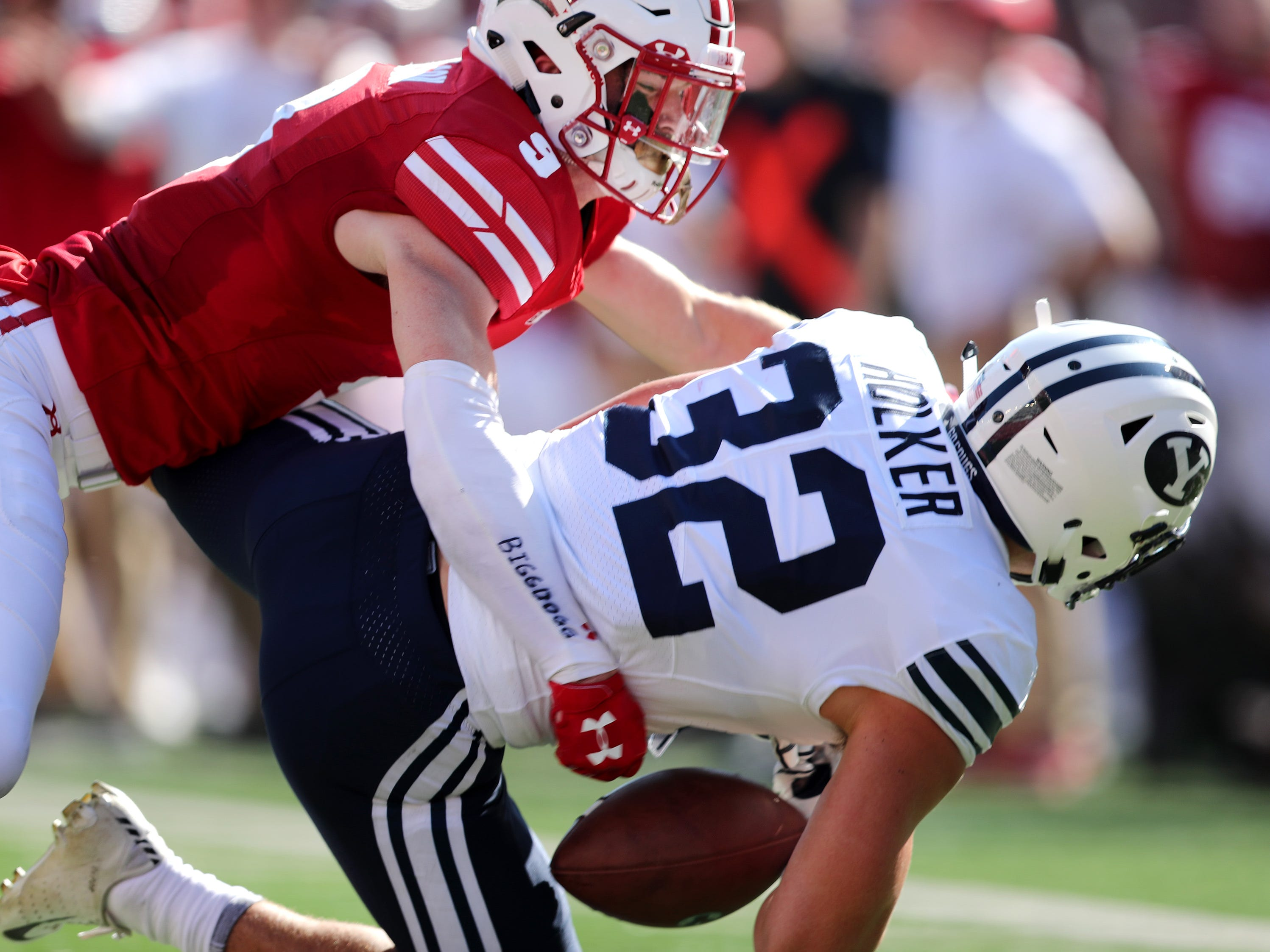 Brigham Young tight end Dallin Holker can't control the ball as he is tackled by Wisconsin safety Scott Nelson.